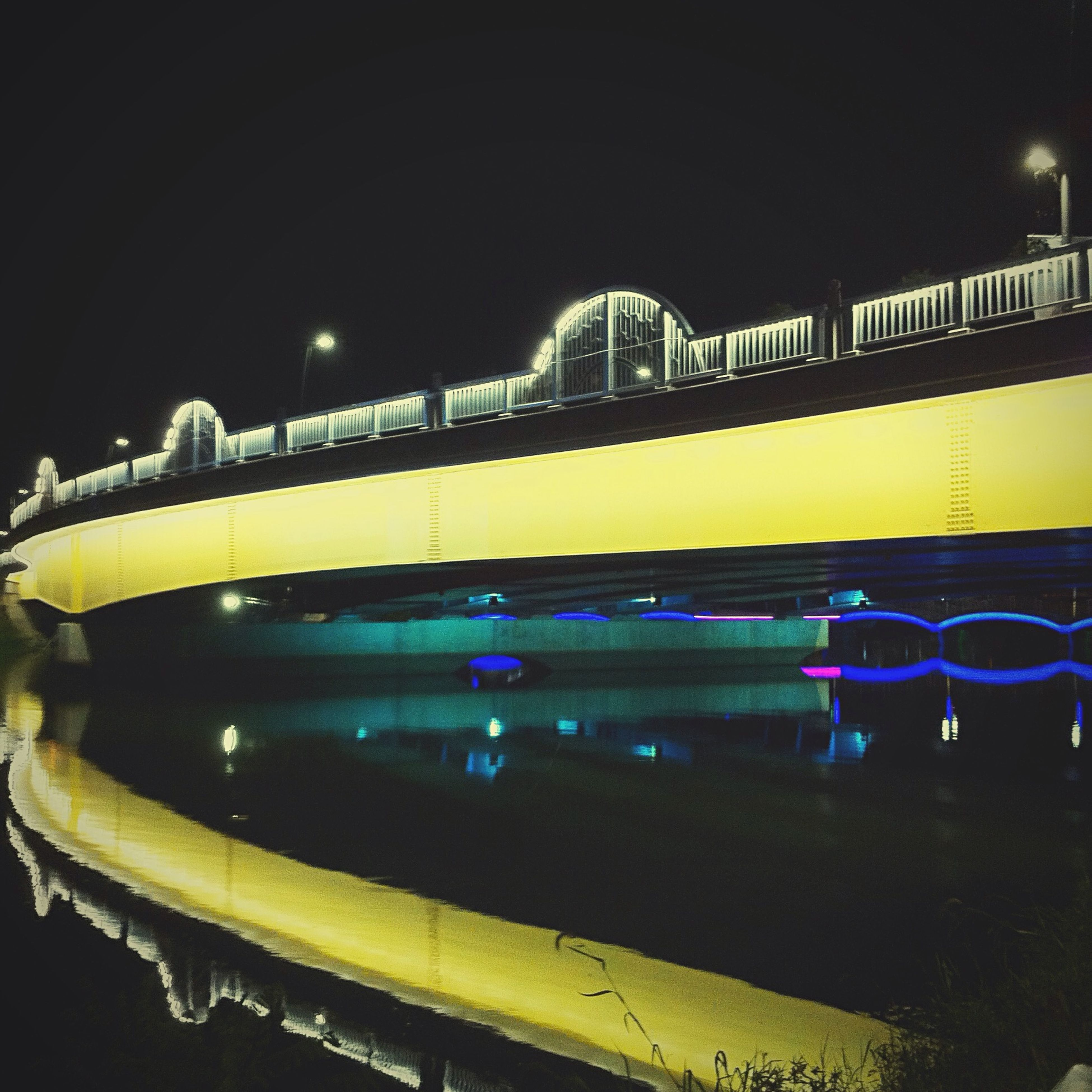 illuminated, night, architecture, built structure, transportation, indoors, yellow, arch, mode of transport, railing, building exterior, railroad station, public transportation, steps, no people, lighting equipment, bridge - man made structure, building, reflection, train - vehicle