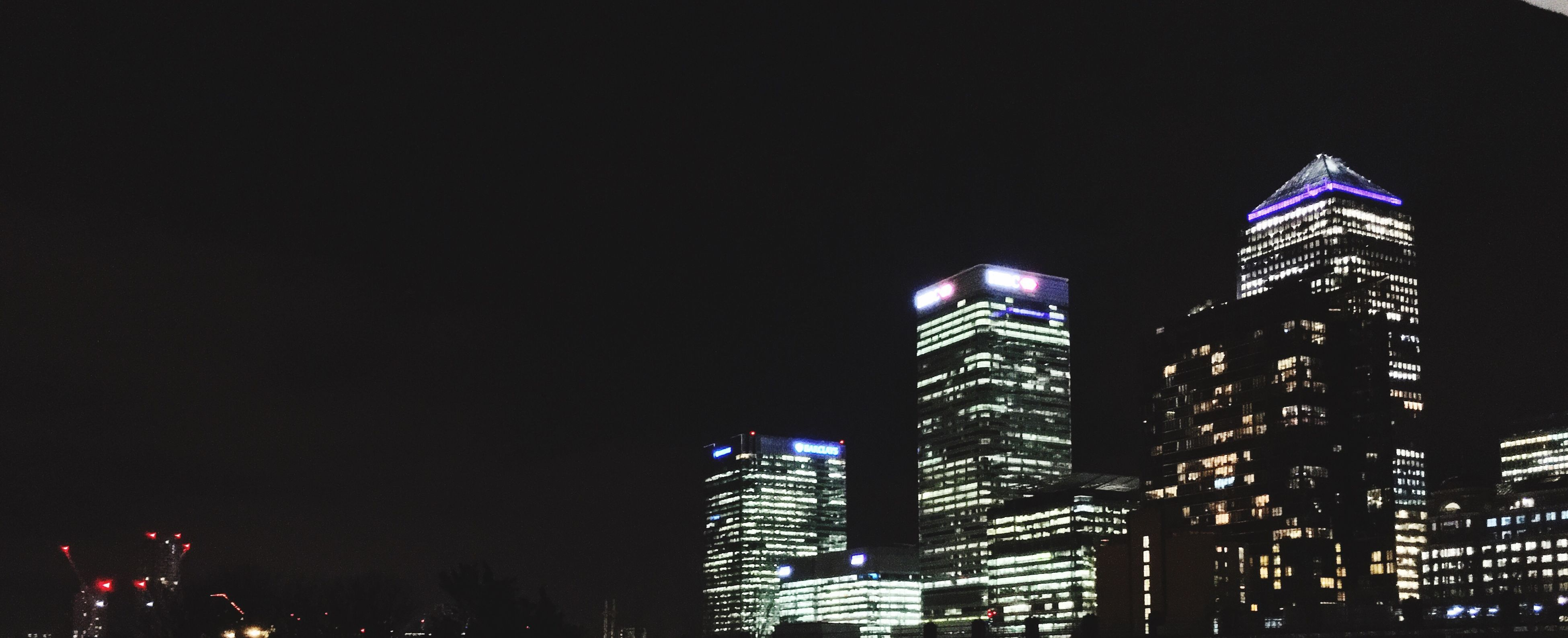 architecture, illuminated, building exterior, built structure, night, skyscraper, city, tall - high, modern, tower, office building, clear sky, low angle view, urban skyline, copy space, capital cities, city life, cityscape, tall, travel destinations
