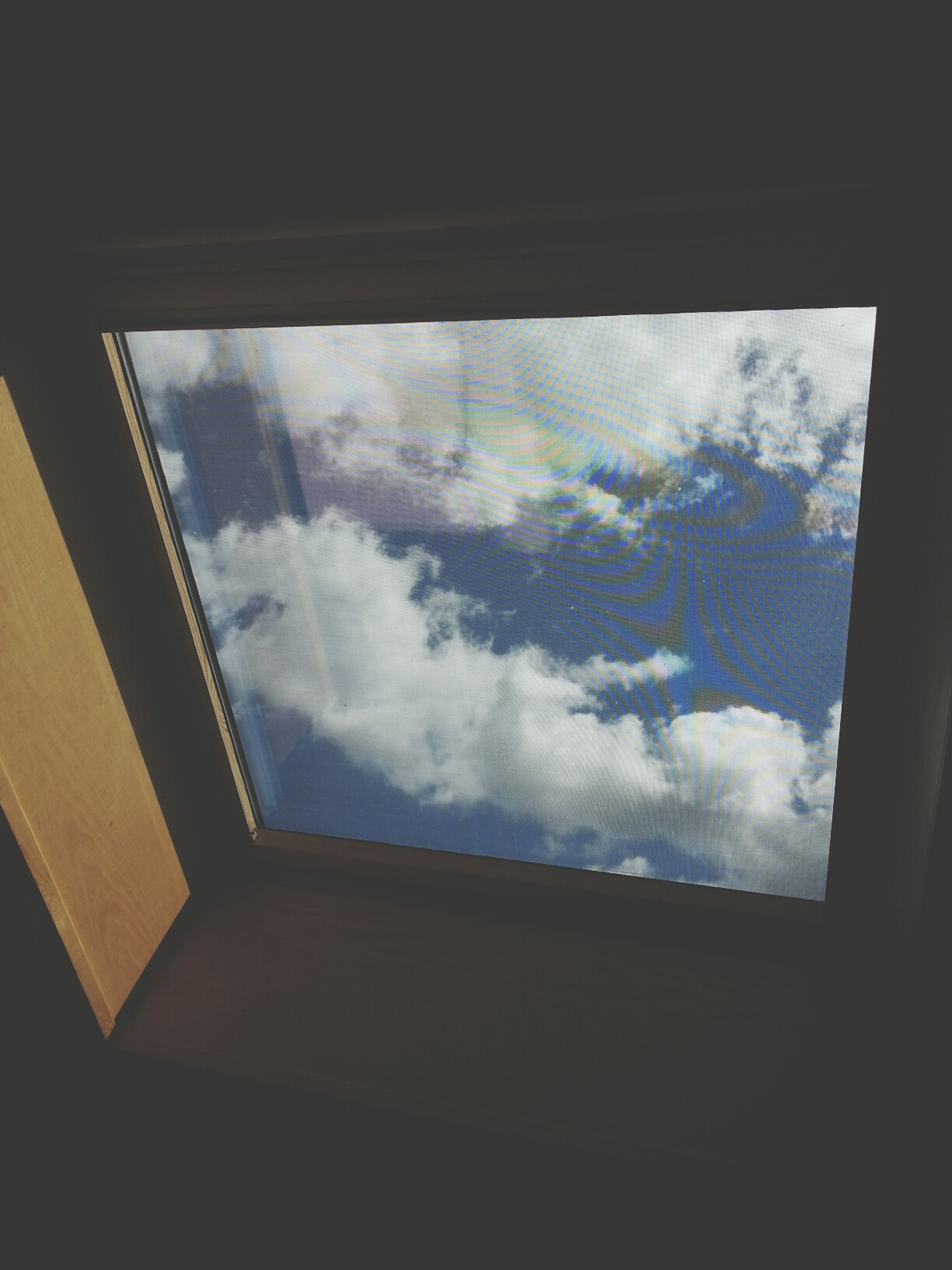 indoors, window, glass - material, transparent, architecture, built structure, sky, low angle view, cloud - sky, glass, day, ceiling, no people, looking through window, building, building exterior, skylight, cloud, reflection, silhouette