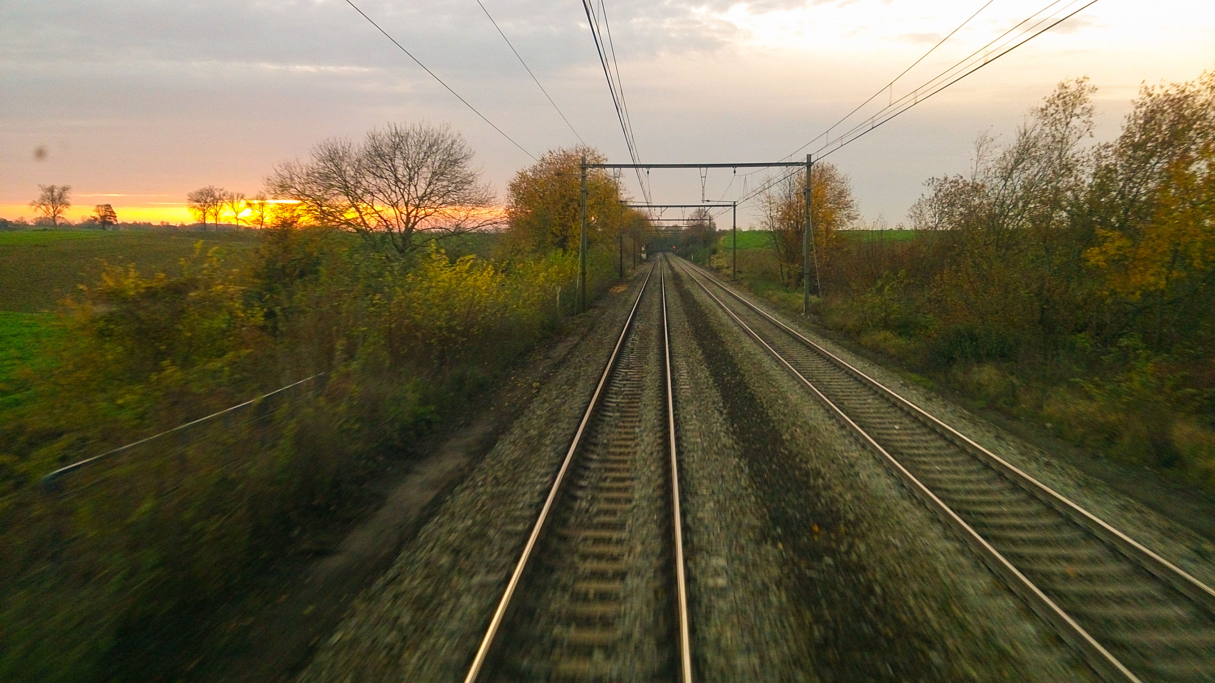 railroad track, rail transportation, the way forward, transportation, diminishing perspective, vanishing point, sky, landscape, tree, electricity pylon, power line, railway track, cloud - sky, growth, nature, field, straight, sunset, public transportation, tranquility