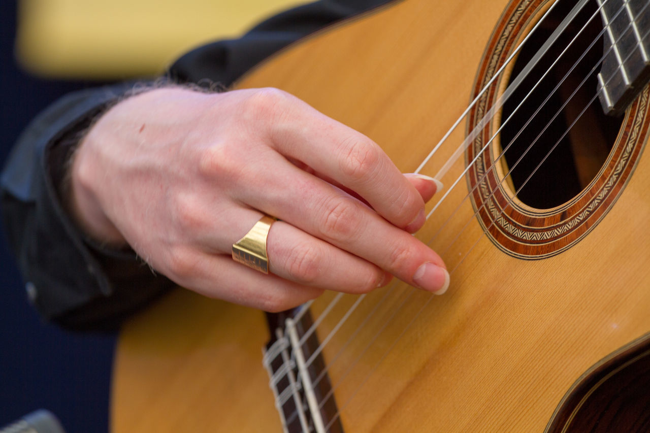 music, musical instrument, guitar, human hand, arts culture and entertainment, playing, musical equipment, musical instrument string, acoustic guitar, plucking an instrument, fretboard, string instrument, musician, one person, real people, human body part, skill, close-up, leisure activity, day, outdoors, people