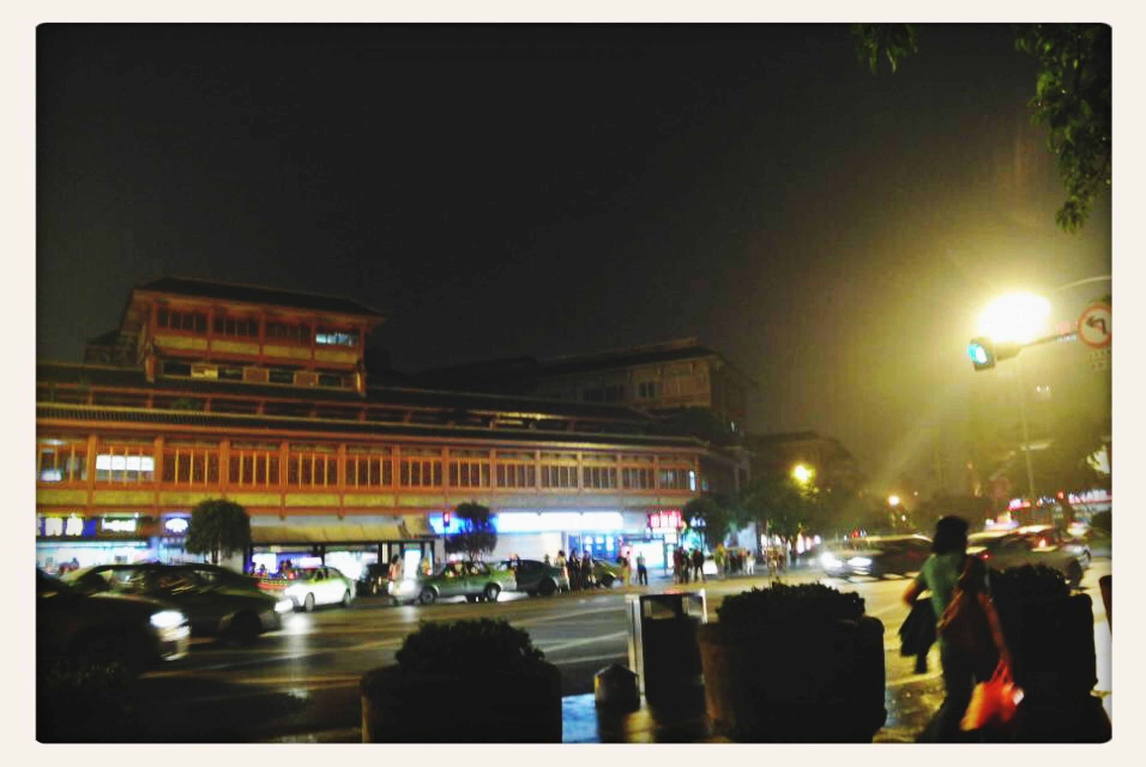 transfer print, illuminated, building exterior, night, architecture, built structure, auto post production filter, city, street, lighting equipment, car, city street, city life, residential building, building, residential structure, street light, land vehicle, incidental people, transportation