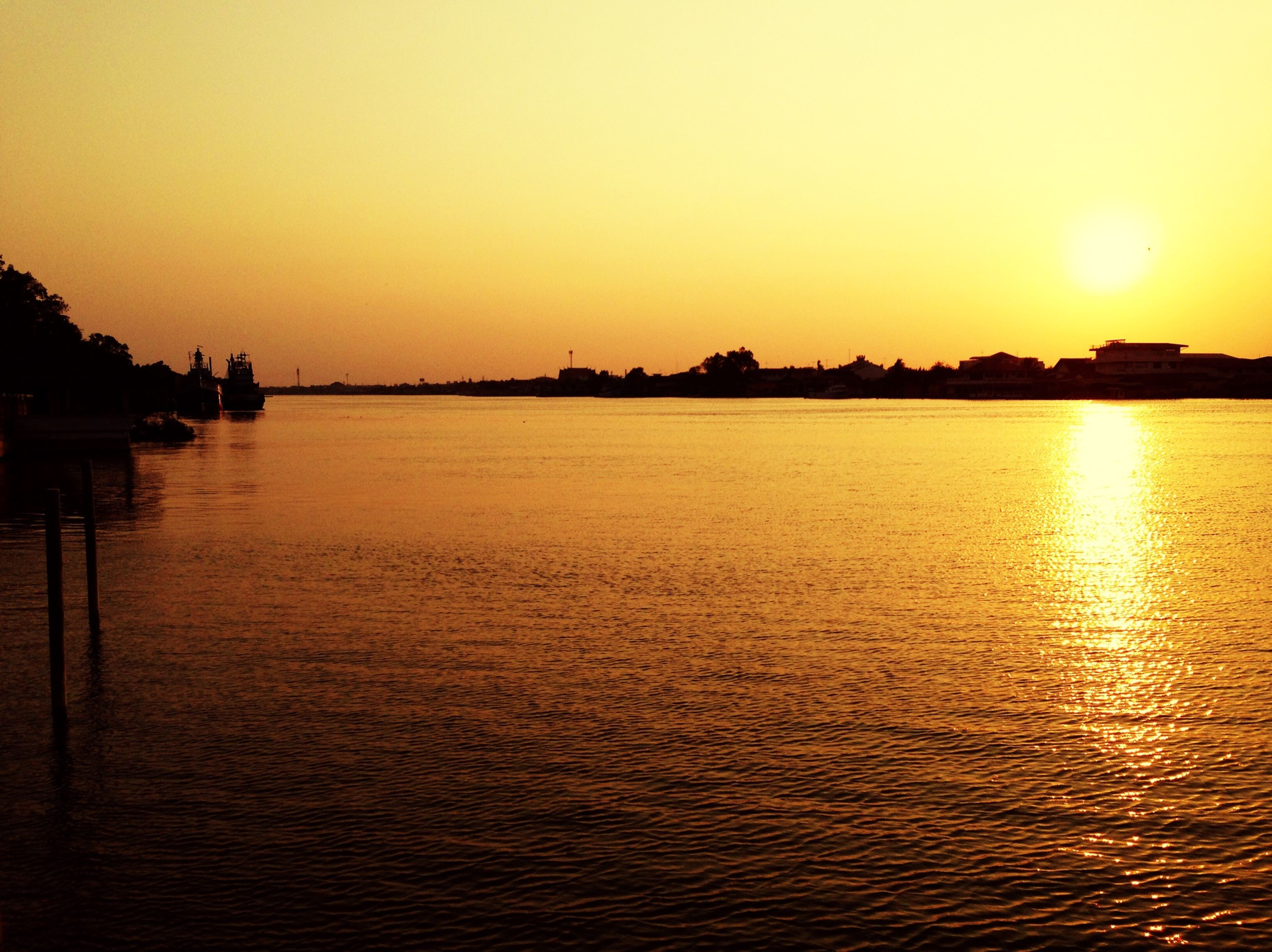 sunset, water, sun, orange color, silhouette, reflection, waterfront, scenics, tranquil scene, tranquility, beauty in nature, clear sky, rippled, built structure, nature, idyllic, sea, river, copy space, sky