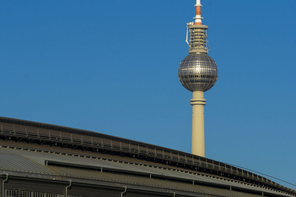 TV Tower with roof of Friedrichstrasse Station in Berlin, Germany Antenna - Aerial Architecture Berlin Blue Broadcasting Building Exterior Built Structure City Clear Sky Color Image Communication Copy Space Cultures Friedrichstrasse Station Germany🇩🇪 Horizontal Low Angle View No People Outdoors Photography Tall - High Tower Travel Travel Destinations Tv Tower Berlin