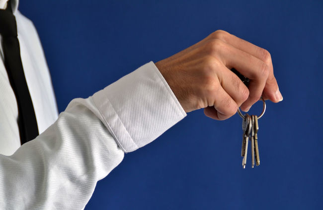 Businessman showing keys on a blue background Blue Blue Background Business Businessman Close-up Commercial Communication Construction Hand House Human Finger Key Keys Lifestyles Man Manager Marketing Office People Person Professional Property Real Estate Sale Studio Shot