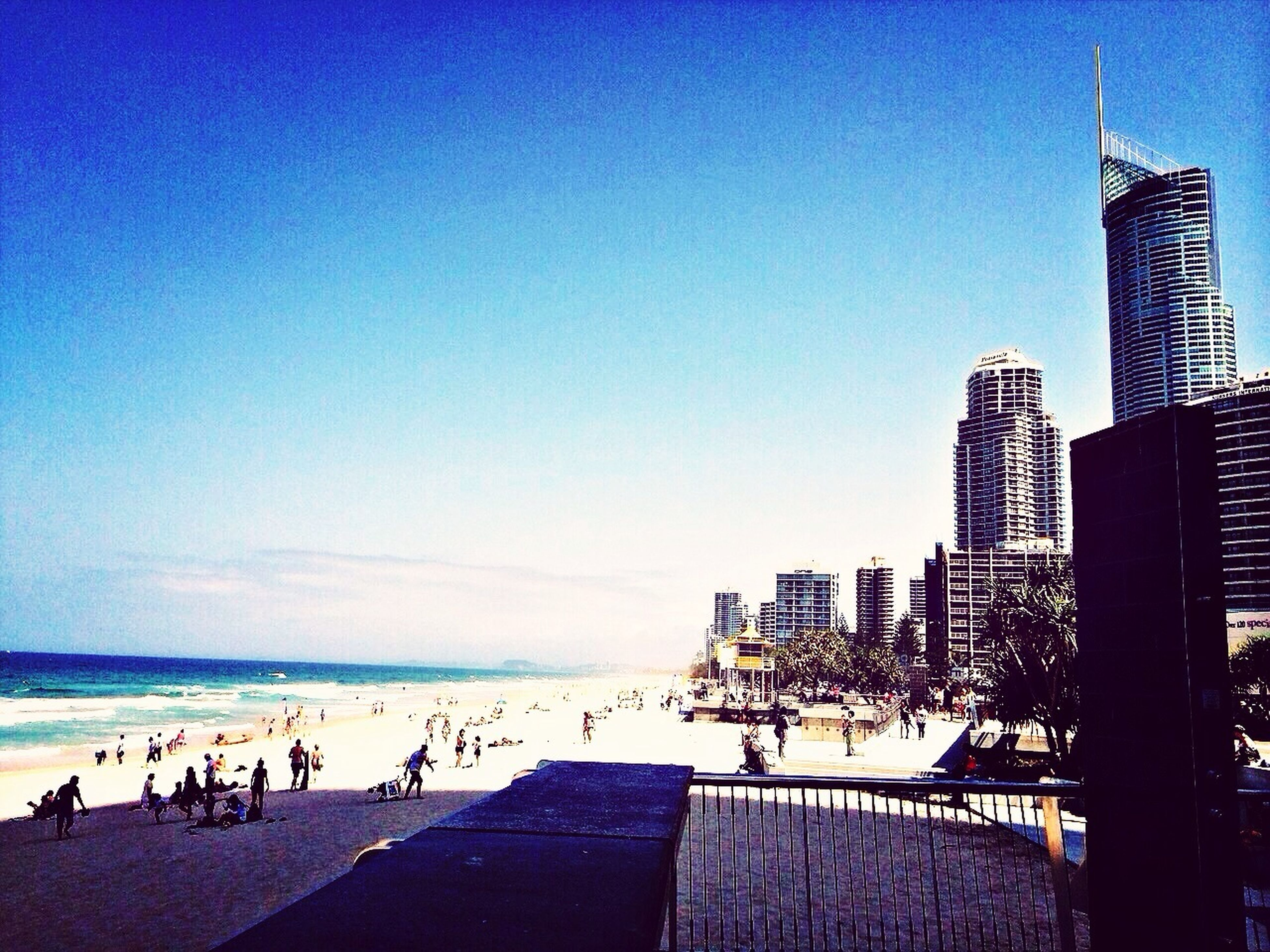 large group of people, sea, building exterior, beach, built structure, architecture, water, clear sky, leisure activity, blue, lifestyles, person, men, copy space, city, vacations, city life, tourist, mixed age range