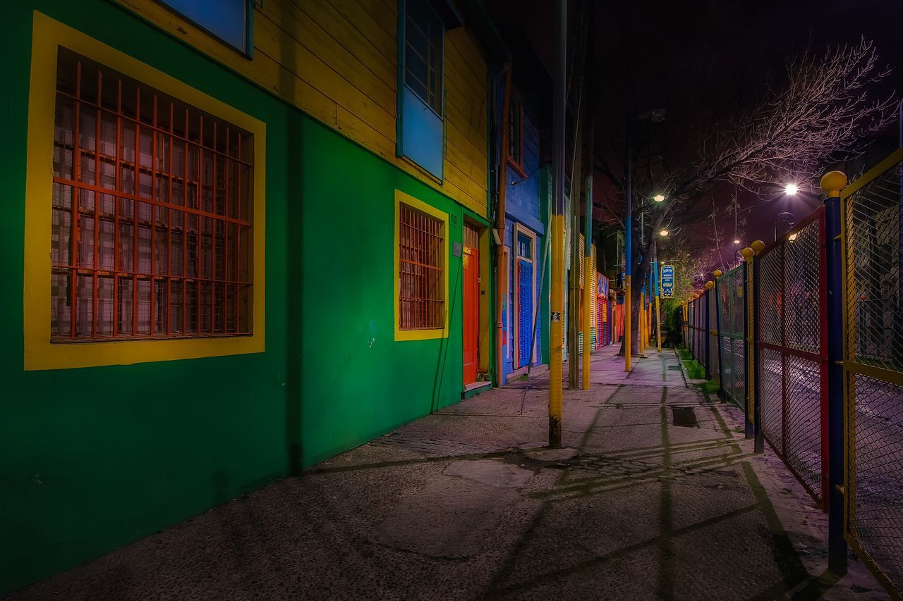 Sidewalk By Multi Colored Buildings In City At Night