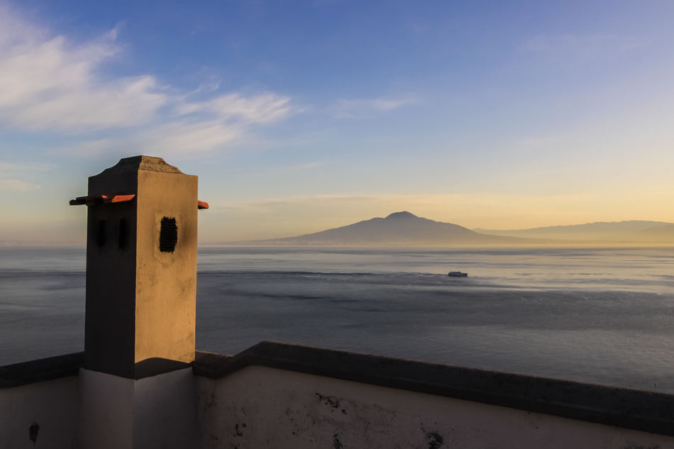 Looking towards Mount Vesuvius across the Bay of Naples from a roof top terrace on the Sorrentine Peninsula, Sorrento, Campania, Italy Love Life, Love Photography Architecture Cloud - Sky Day Horizon Over Water Mountain Nature No People Outdoors Scenics Sea Sky Sunset Tranquil Scene Tranquility Water Sorrento Italia Italy Terrace Rooftop Naples Stack Chimney Roof Villa