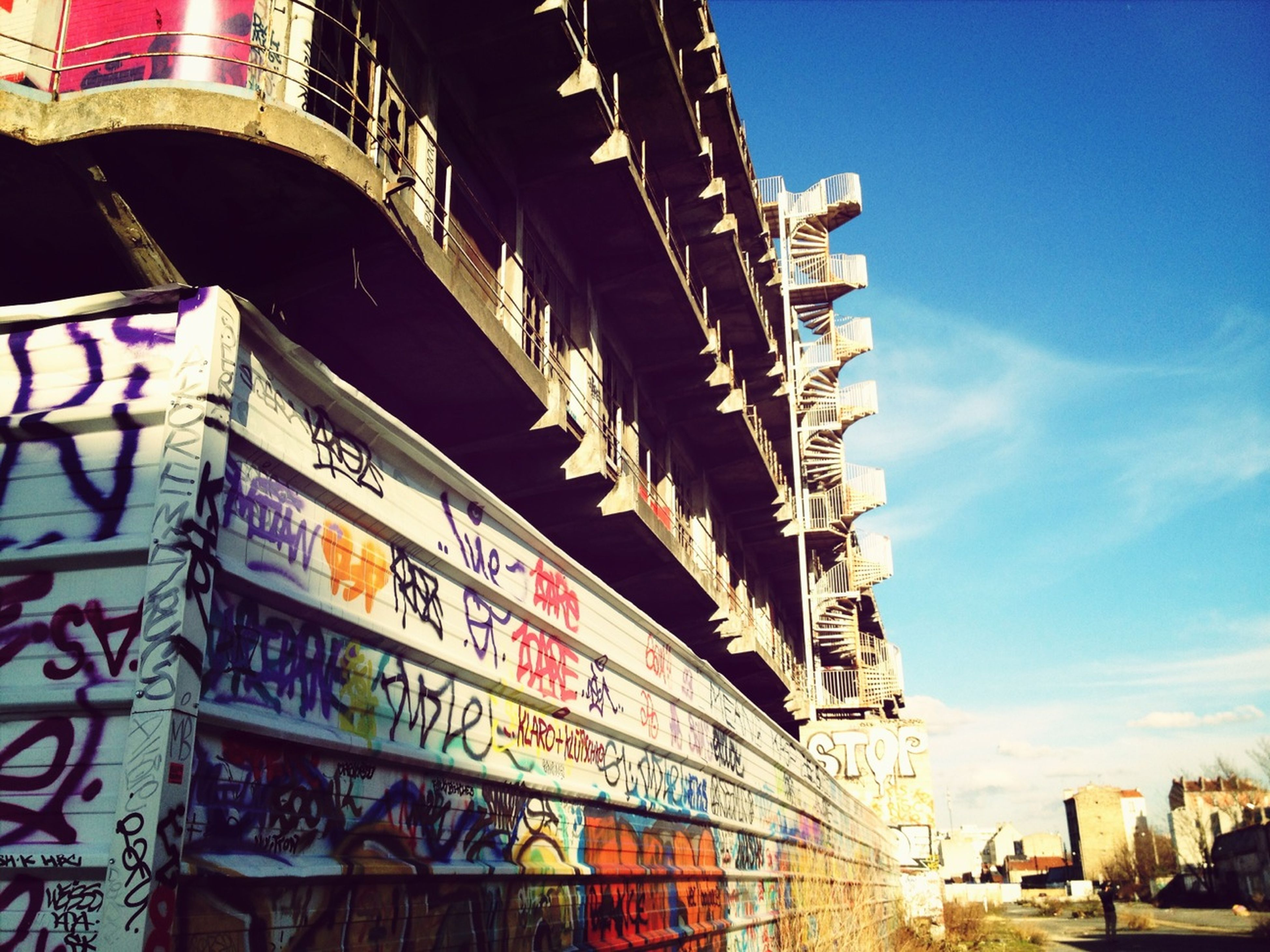 architecture, built structure, building exterior, low angle view, transportation, text, city, sky, western script, graffiti, day, building, outdoors, incidental people, clear sky, blue, no people, street, city life, non-western script