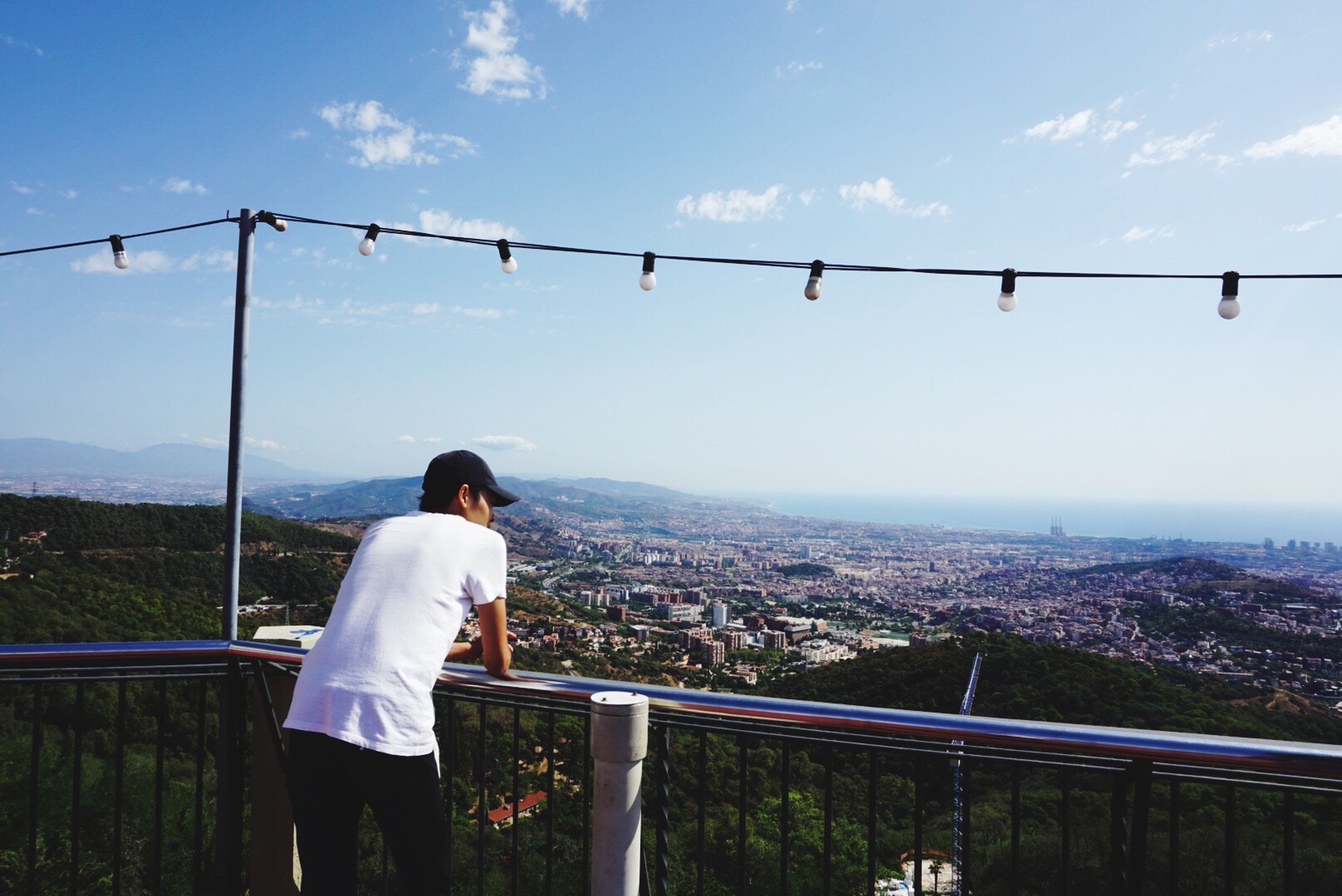 childhood, leisure activity, rear view, standing, lifestyles, sky, landscape, built structure, balcony, looking at view, railing, casual clothing, blue, cityscape, cloud - sky, mountain, looking, day, scenics, outdoors, carefree, remote, observation point, nature