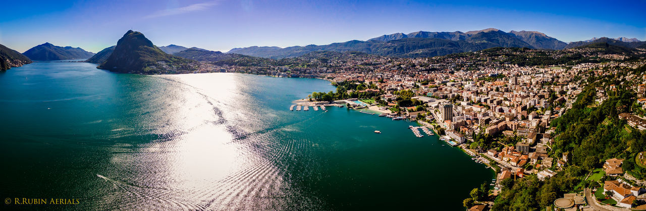 Battle Of The Cities Water Mountain Tranquil Scene Scenics Sea Tranquility Blue Beauty In Nature Panoramic Mountain Range Lake Nature Waterfront Sky Outdoors Day Coastline Bay Of Water Seascape Lugano Luganolake Aerial View Aerial Shot