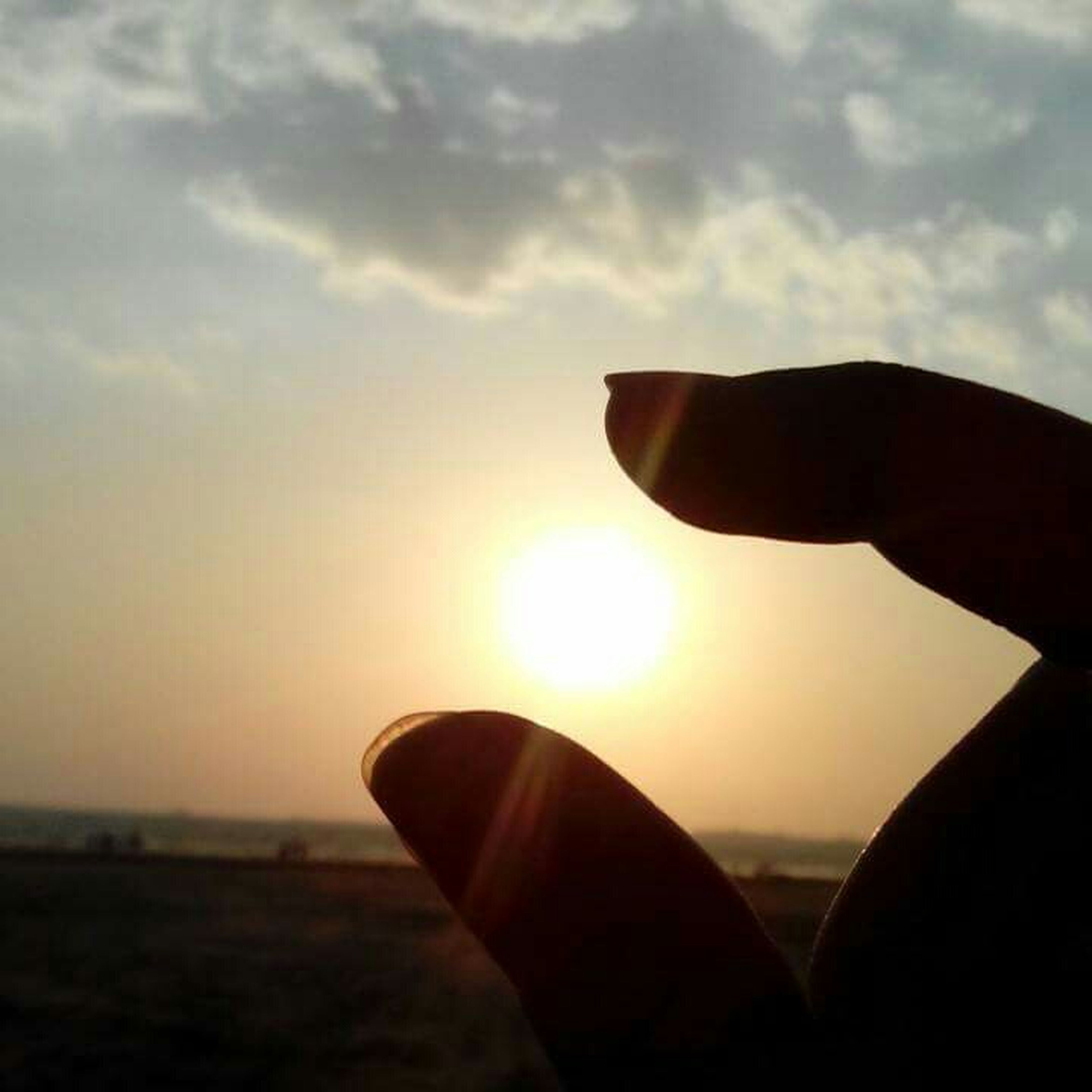 sunset, person, sky, sun, part of, personal perspective, cropped, unrecognizable person, human finger, sunlight, close-up, focus on foreground, silhouette, orange color, cloud - sky, lens flare, nature