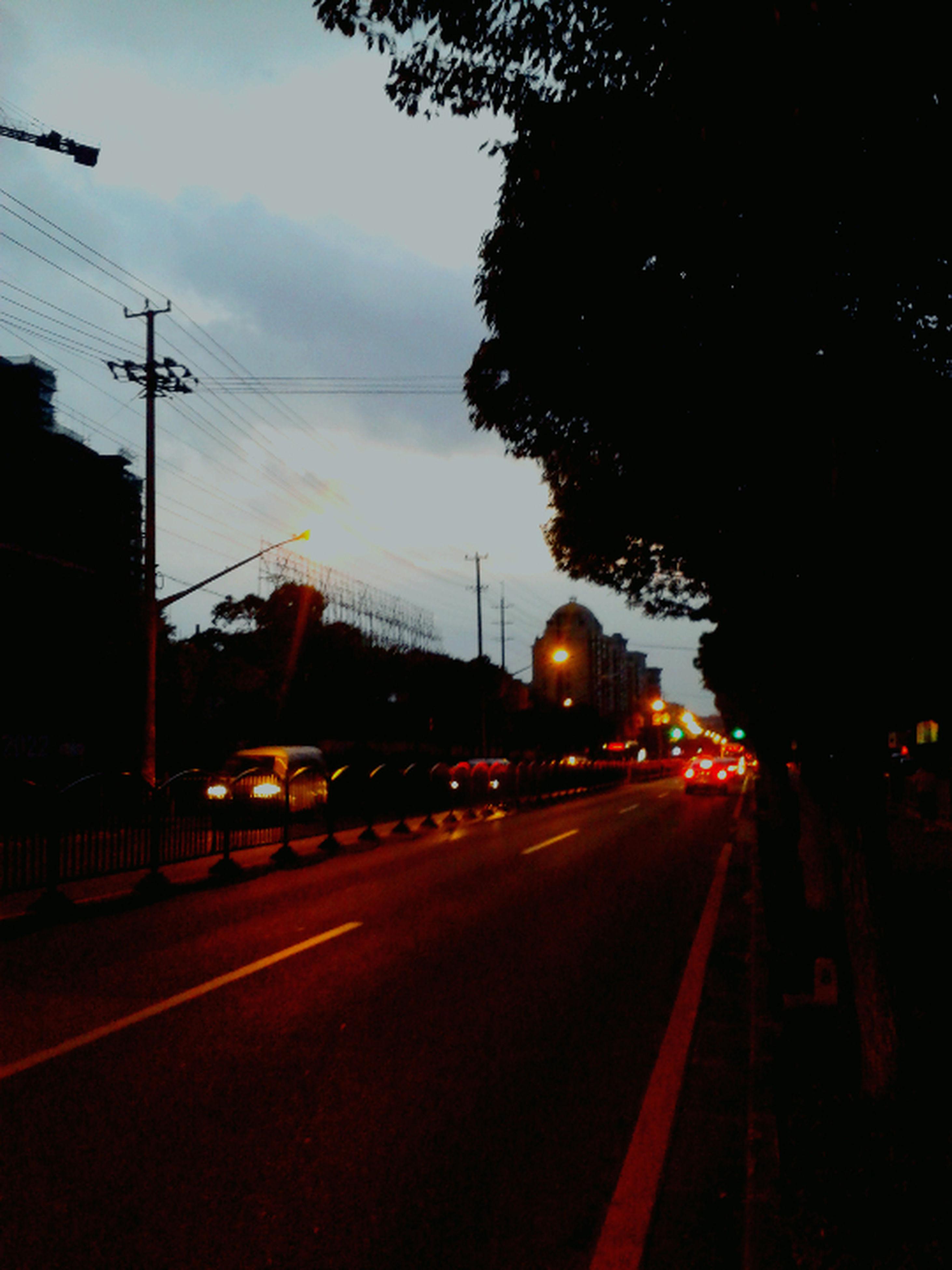 transportation, mode of transport, car, land vehicle, road, sky, illuminated, street light, street, the way forward, on the move, sunset, silhouette, road marking, dusk, diminishing perspective, tree, traffic, electricity pylon, power line