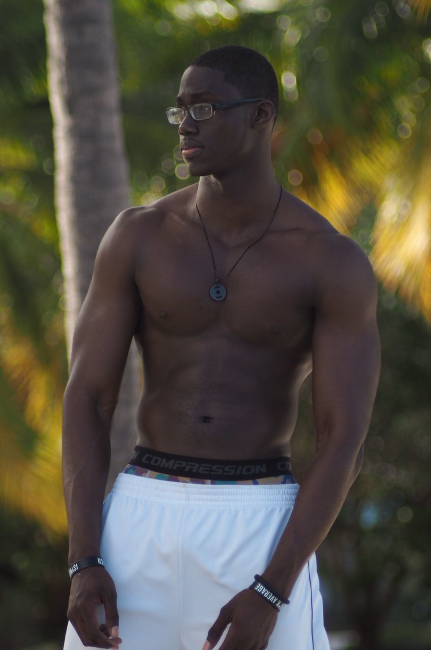 young men, young adult, real people, one person, standing, three quarter length, front view, lifestyles, fashion, mid adult men, leisure activity, outdoors, shirtless, tree, nature, day