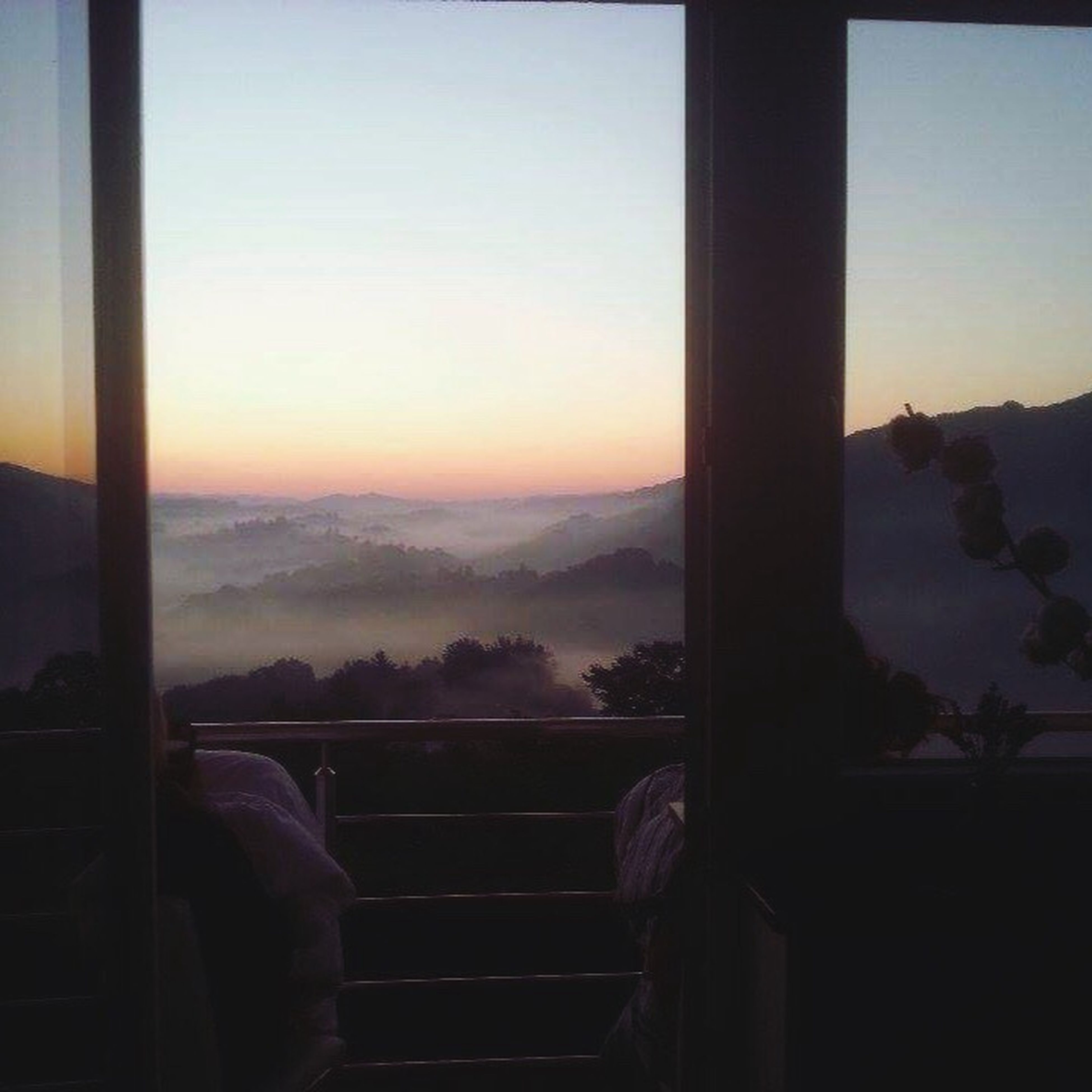 window, sunset, indoors, sky, scenics, transparent, orange color, mountain, cloud, tranquil scene, tranquility, nature, beauty in nature, mountain range, cloudscape, remote, cloud - sky, romantic sky