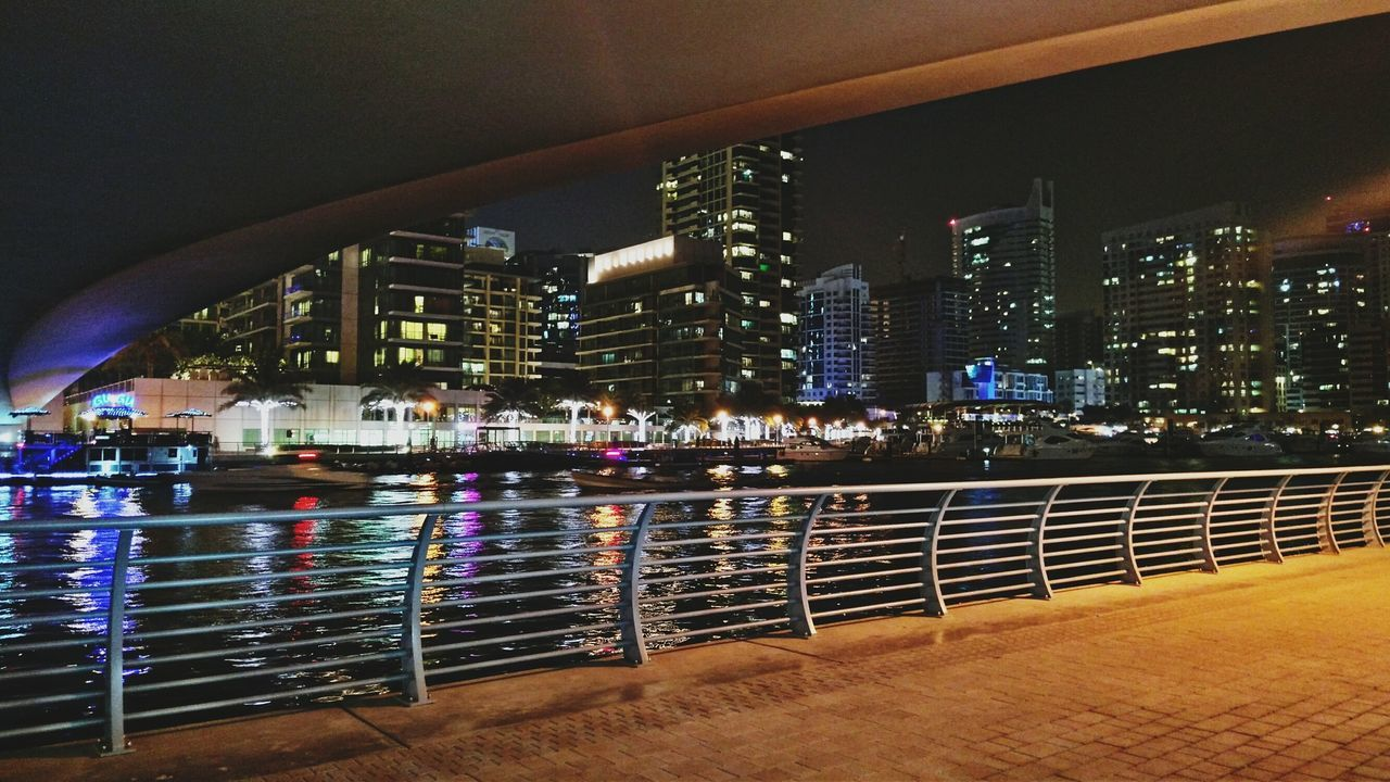 architecture, railing, built structure, city, river, building exterior, water, illuminated, skyscraper, cityscape, modern, no people, night, outdoors