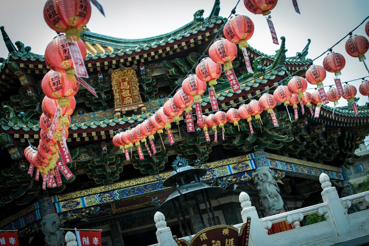 cultures, hanging, low angle view, chinese lantern, architecture, built structure, lantern, roof, spirituality, building exterior, tradition, celebration, place of worship, religion, dragon, eaves, traditional festival, chinese new year, chinese lantern festival, chinese dragon, day, no people, outdoors, sky