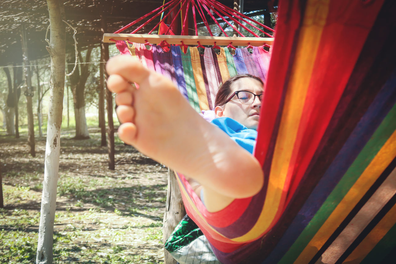 multi colored, one person, real people, human hand, leisure activity, day, outdoors, tree, lifestyles, close-up, young adult