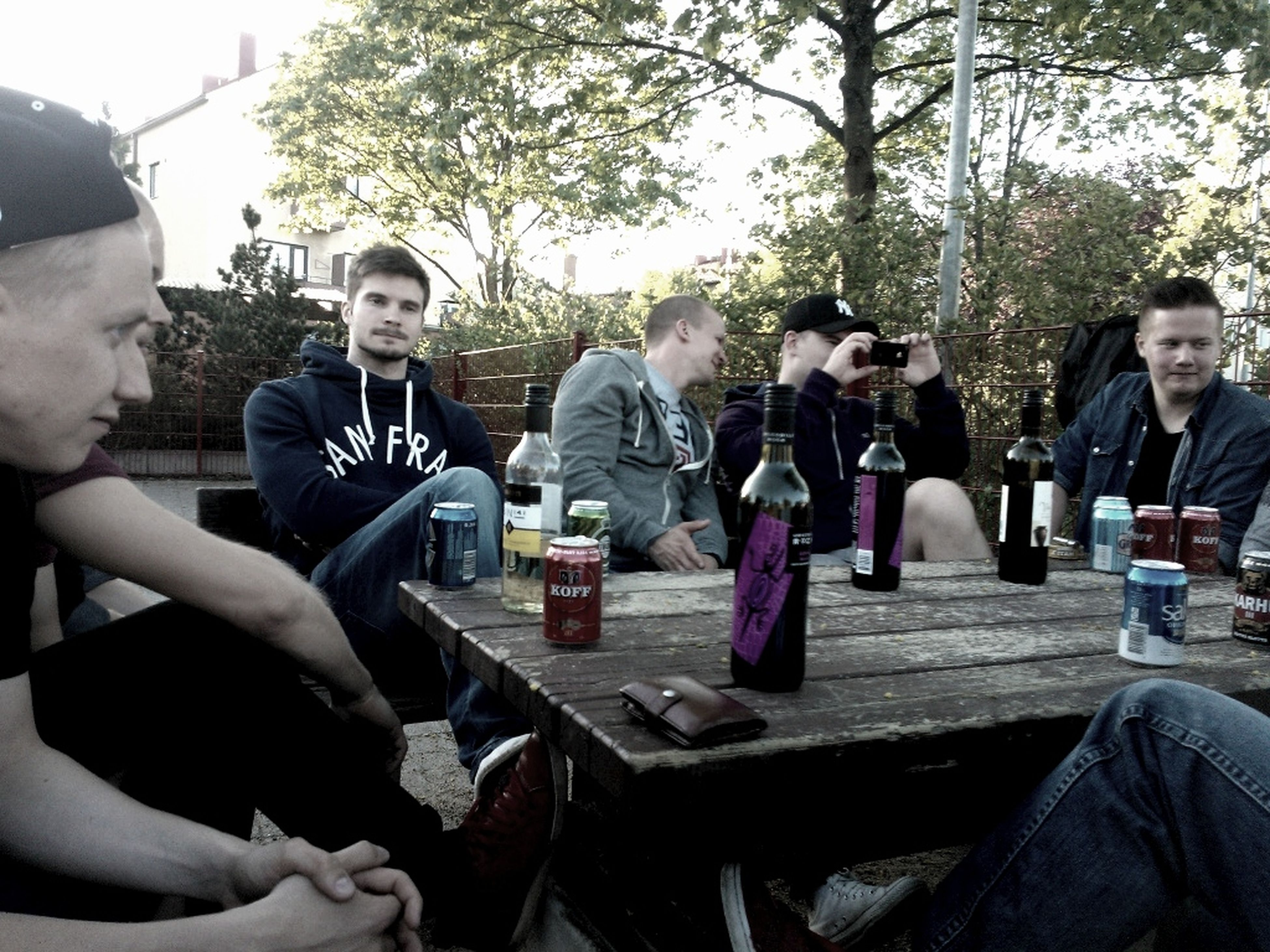 lifestyles, leisure activity, togetherness, casual clothing, friendship, bonding, sitting, person, young adult, love, tree, smiling, young men, portrait, looking at camera, happiness