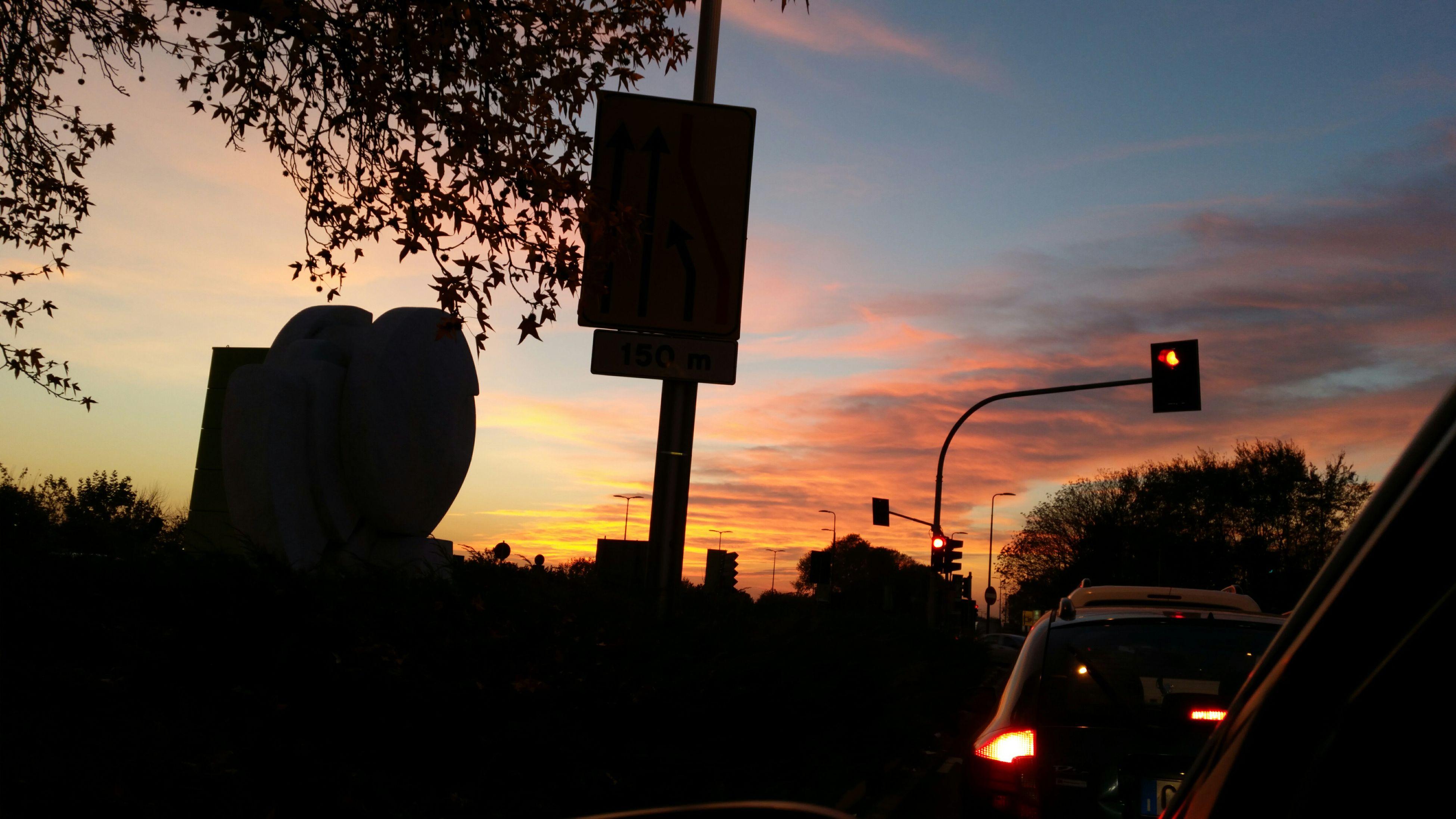 silhouette, sunset, tree, sky, communication, street light, building exterior, built structure, road sign, architecture, cloud - sky, dusk, low angle view, orange color, city, guidance, car, cloud, dark, street