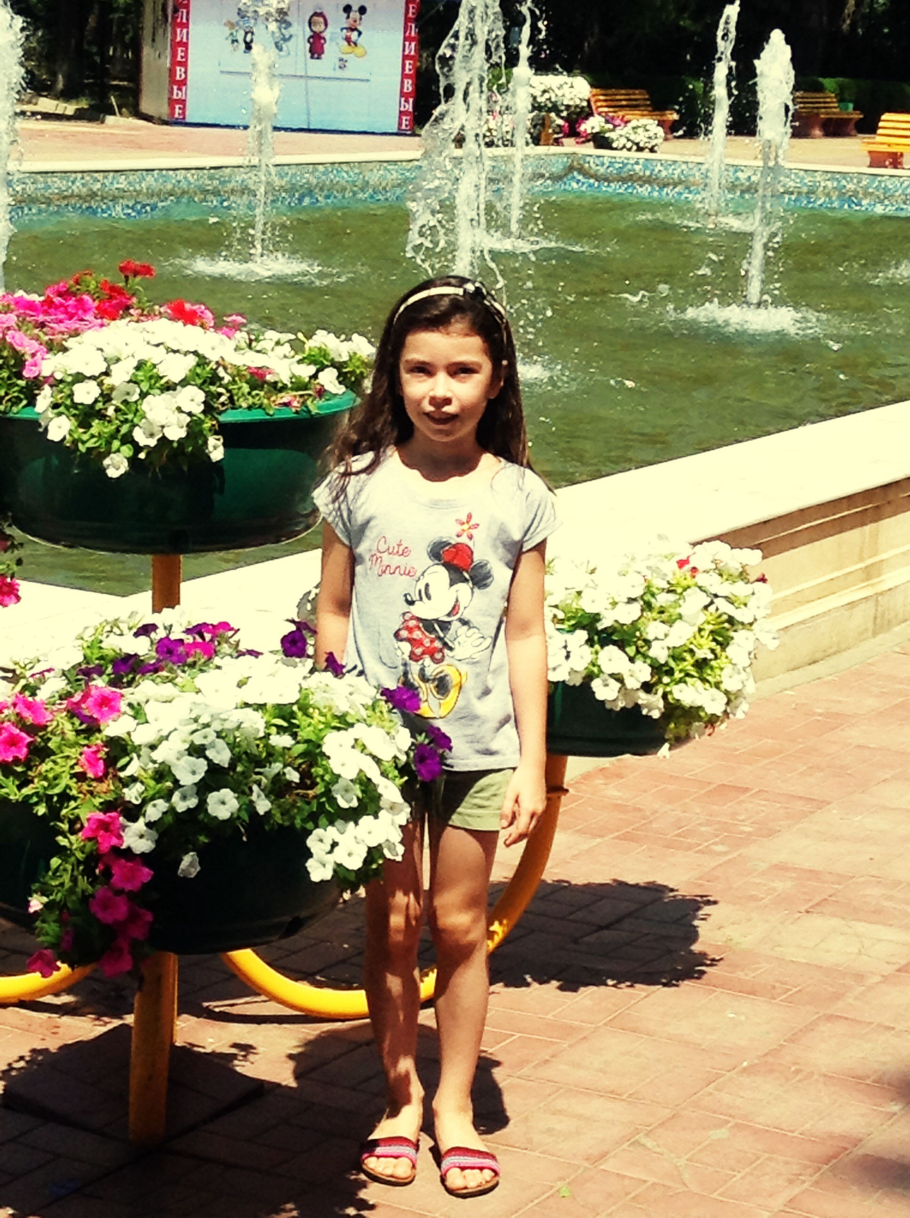flower, full length, standing, smiling, girls, lifestyles, leisure activity, childhood, potted plant, person, front view, portrait, casual clothing, elementary age, holding, looking at camera, freshness, plant, day, bouquet, long hair, outdoors, beauty, vacations