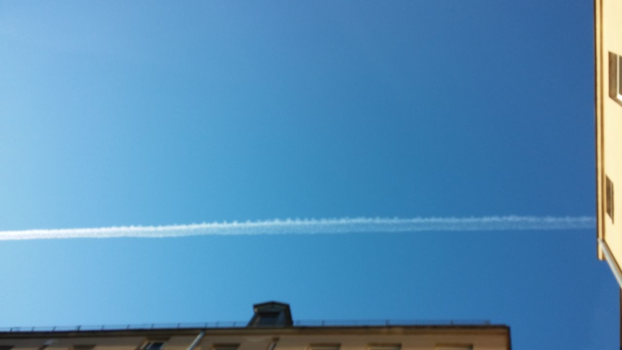 blue, vapor trail, built structure, contrail, low angle view, day, outdoors, no people, architecture, building exterior, nature, clear sky, sky, beauty in nature