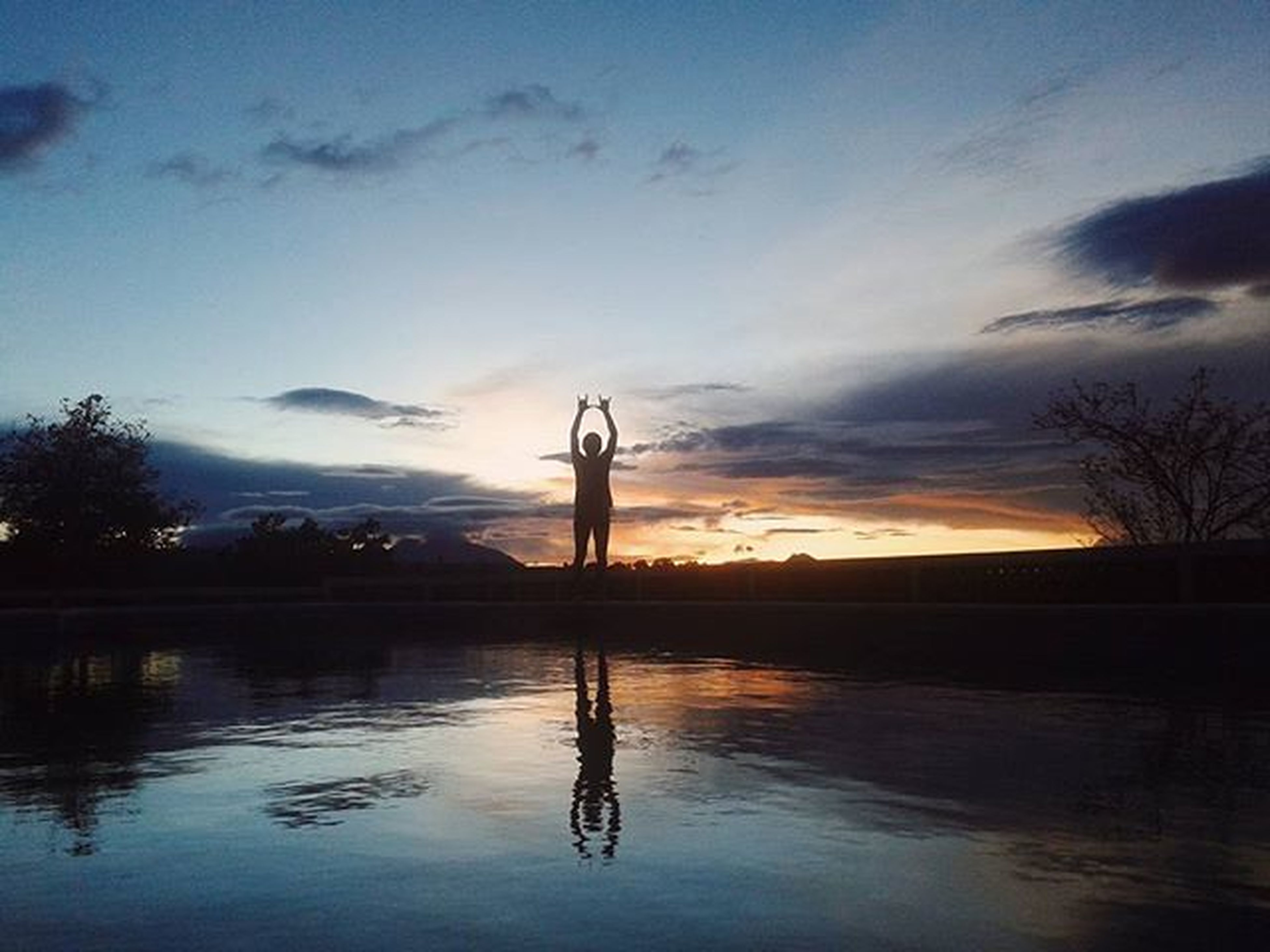 water, silhouette, sky, reflection, sunset, cloud - sky, lake, waterfront, tranquility, cloud, tranquil scene, nature, dusk, scenics, one person, built structure, statue, beauty in nature, full length, outdoors
