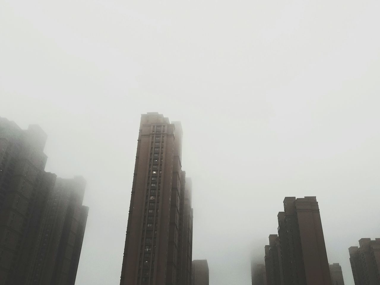 skyscraper, architecture, fog, city, building exterior, built structure, foggy, weather, modern, copy space, mist, no people, urban skyline, day, outdoors, low angle view, cityscape, downtown district, tall, sky, nature