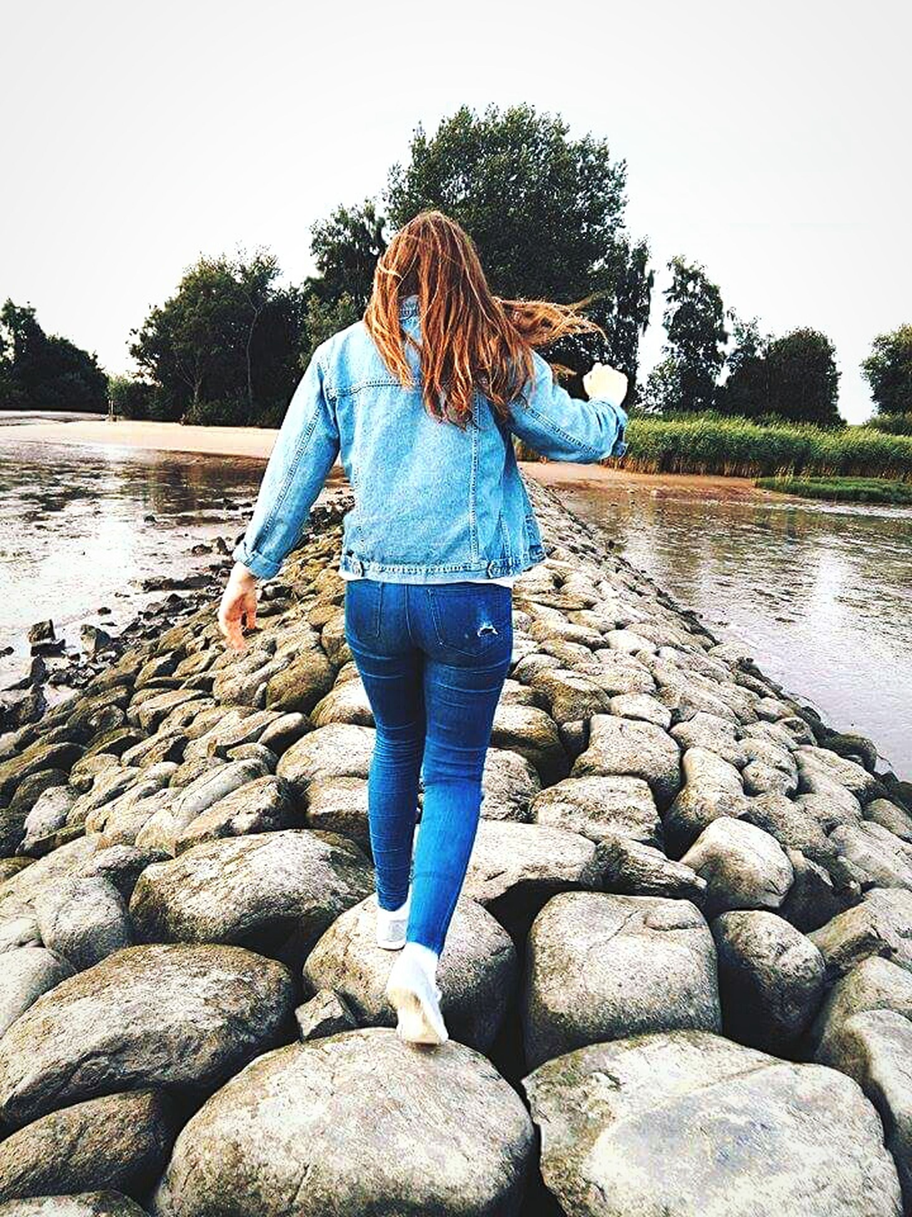 water, lifestyles, rear view, full length, casual clothing, standing, leisure activity, rock - object, lake, tree, person, nature, tranquility, tranquil scene, beauty in nature, river, day, clear sky