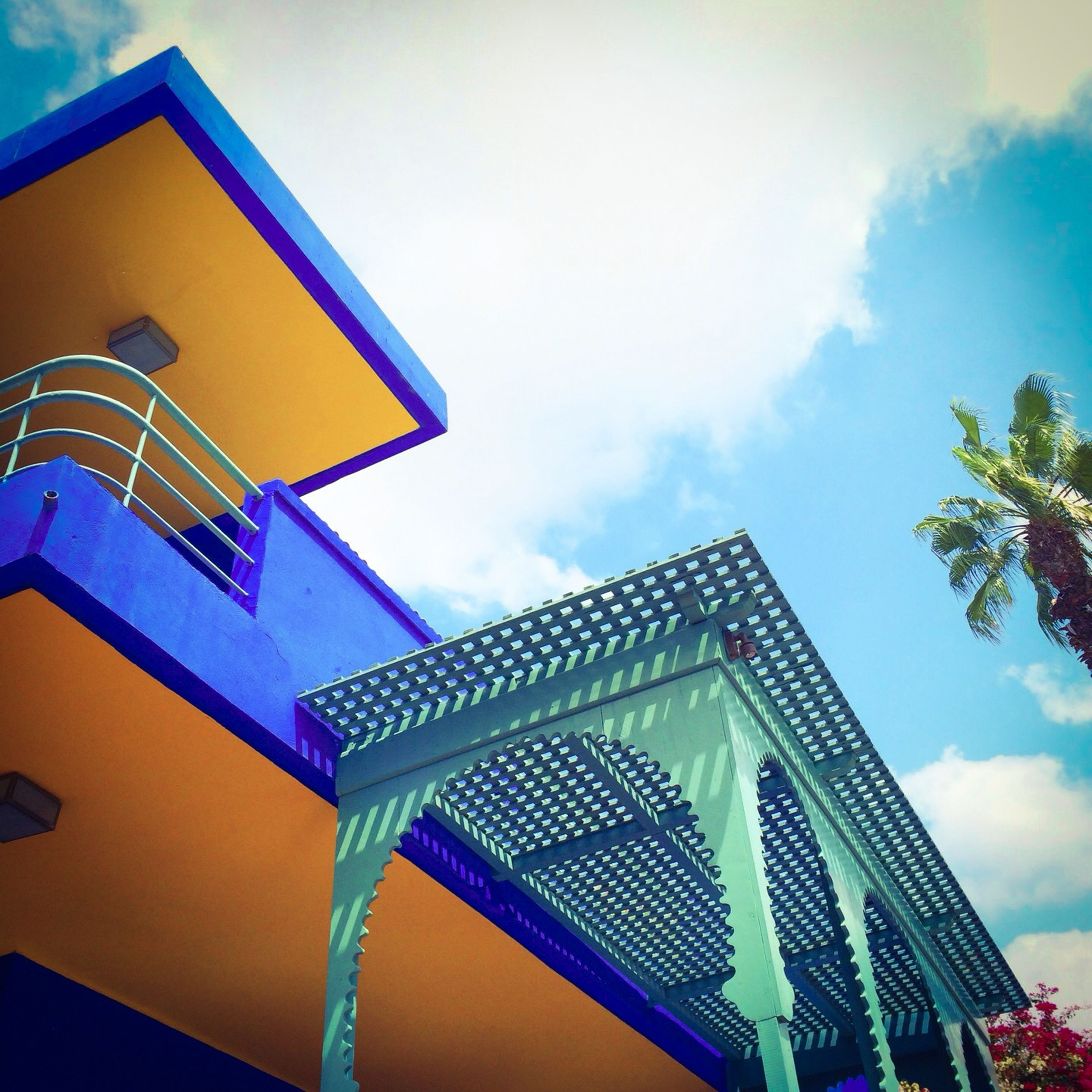 low angle view, architecture, built structure, building exterior, sky, blue, multi colored, cloud - sky, cloud, building, day, outdoors, high section, no people, pattern, art and craft, window, cloudy, house, design
