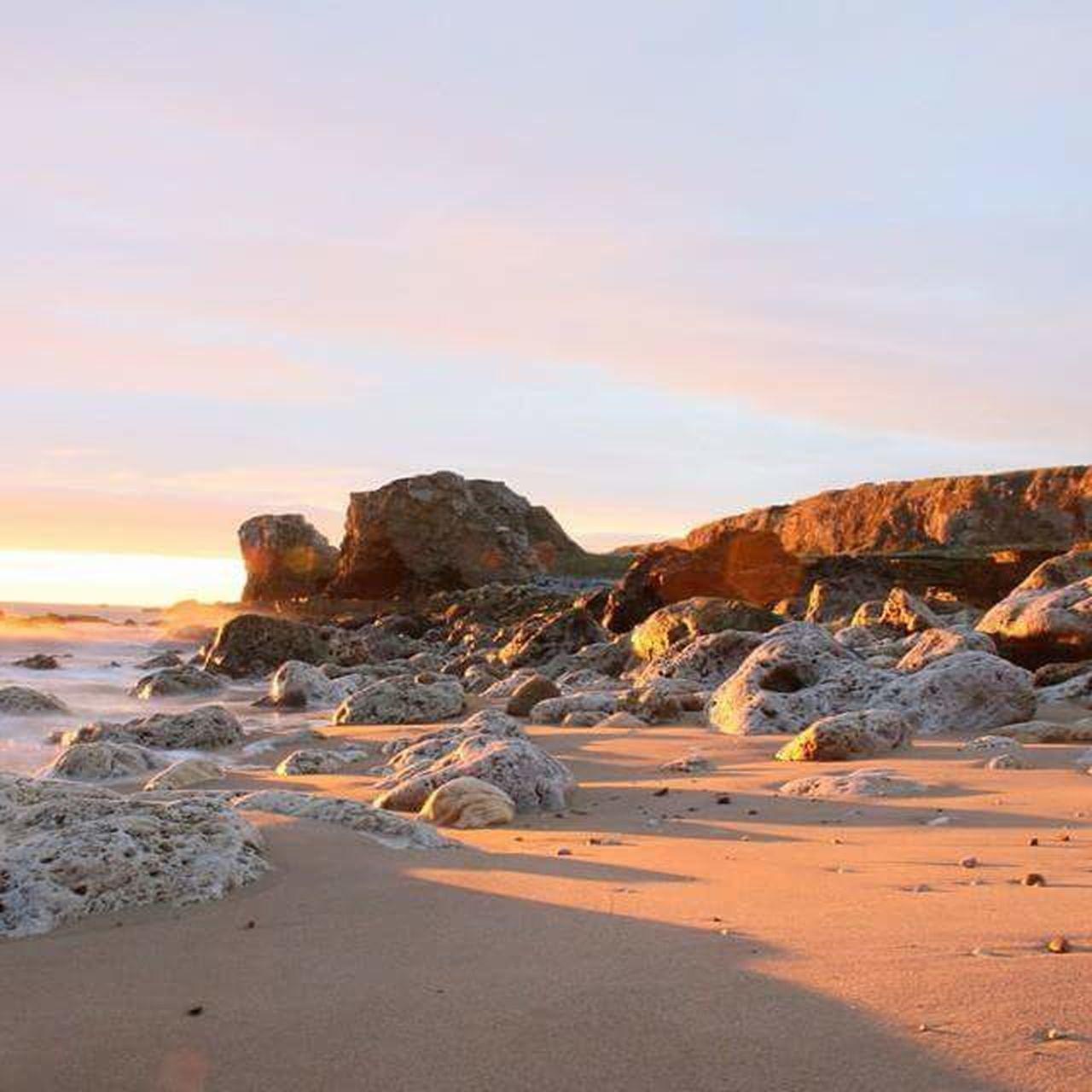 Sun sunrise seaside shoreline coastline coastal scene coast scenic reflections water sun ray sunbeam rock pebbles cliff sand shingle long exposure view tranquil calming relaxing nature fresh