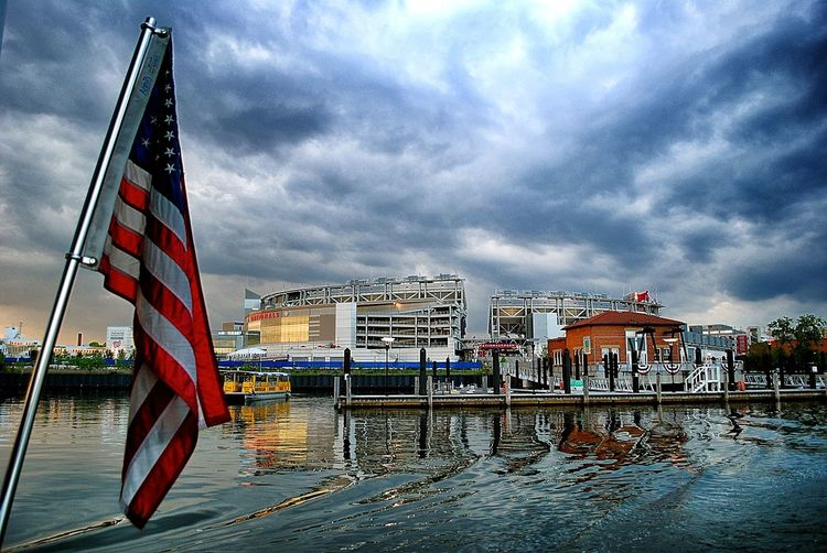 American Flag Architecture Baseball Blue Building Exterior Building Story Built Structure City Cloud Cloud - Sky Cloudy Day Development Flag Modern Multi Colored National Flag No People Outdoors Rippled Sea Sky Stadium Water Waterfront