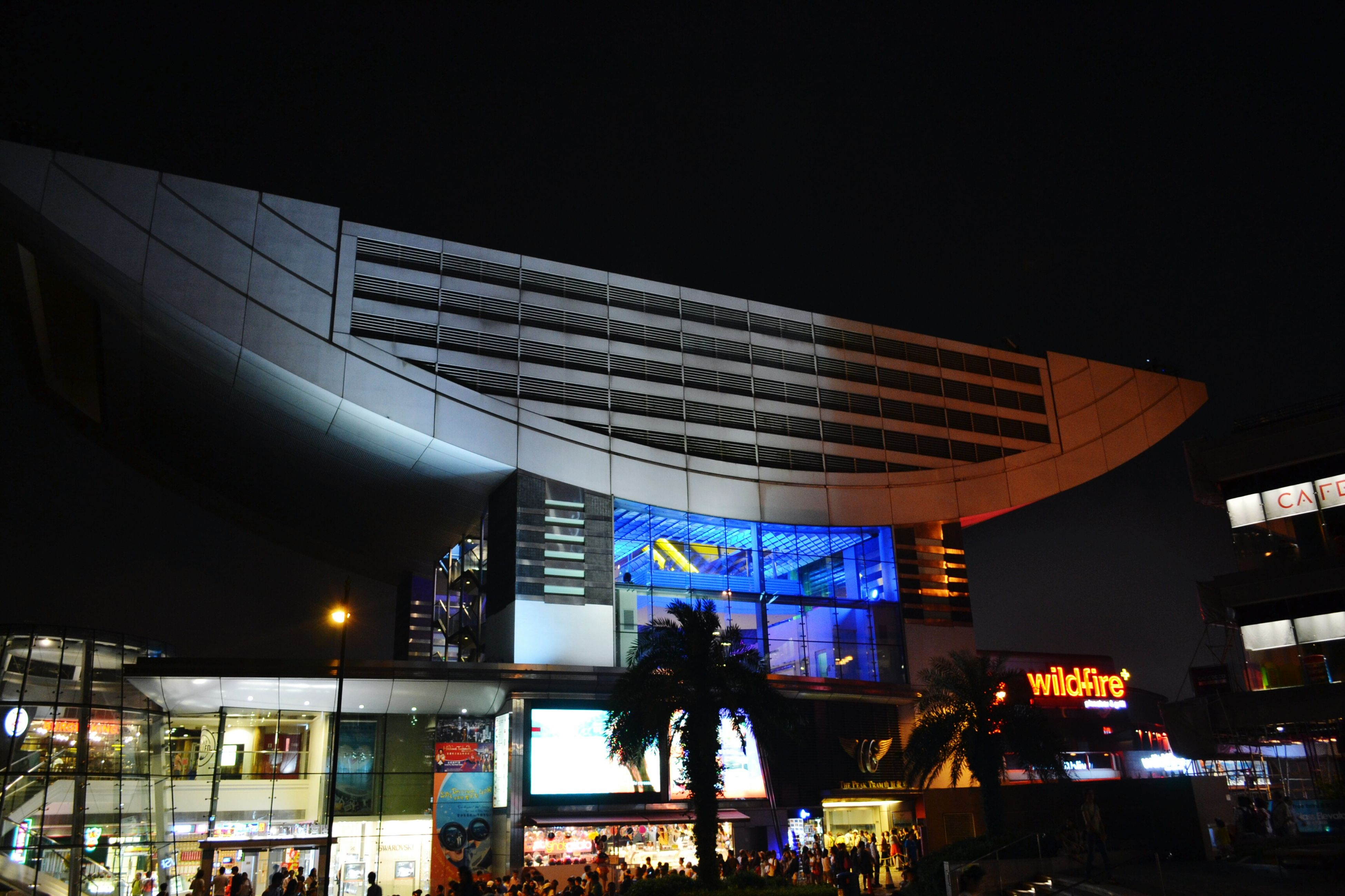 architecture, built structure, illuminated, building exterior, night, low angle view, city, modern, clear sky, building, city life, lighting equipment, text, incidental people, outdoors, sky, arts culture and entertainment, street light, transportation, copy space