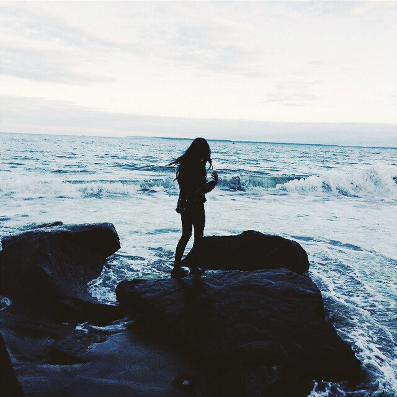 sea, horizon over water, water, one person, beach, nature, tranquil scene, beauty in nature, real people, scenics, rock - object, standing, sky, full length, tranquility, leisure activity, idyllic, silhouette, outdoors, lifestyles, women, wave, day, vacations, young women, young adult, people