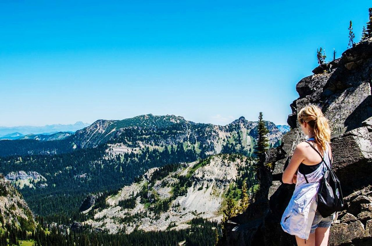 leisure activity, mountain, young adult, real people, one person, young women, lifestyles, nature, adventure, rock - object, standing, tree, day, casual clothing, rear view, beauty in nature, outdoors, scenics, full length, clear sky, blue, women, sky, beautiful woman, blond hair, vacations, rock climbing, one young woman only, one woman only, adult, adults only, people