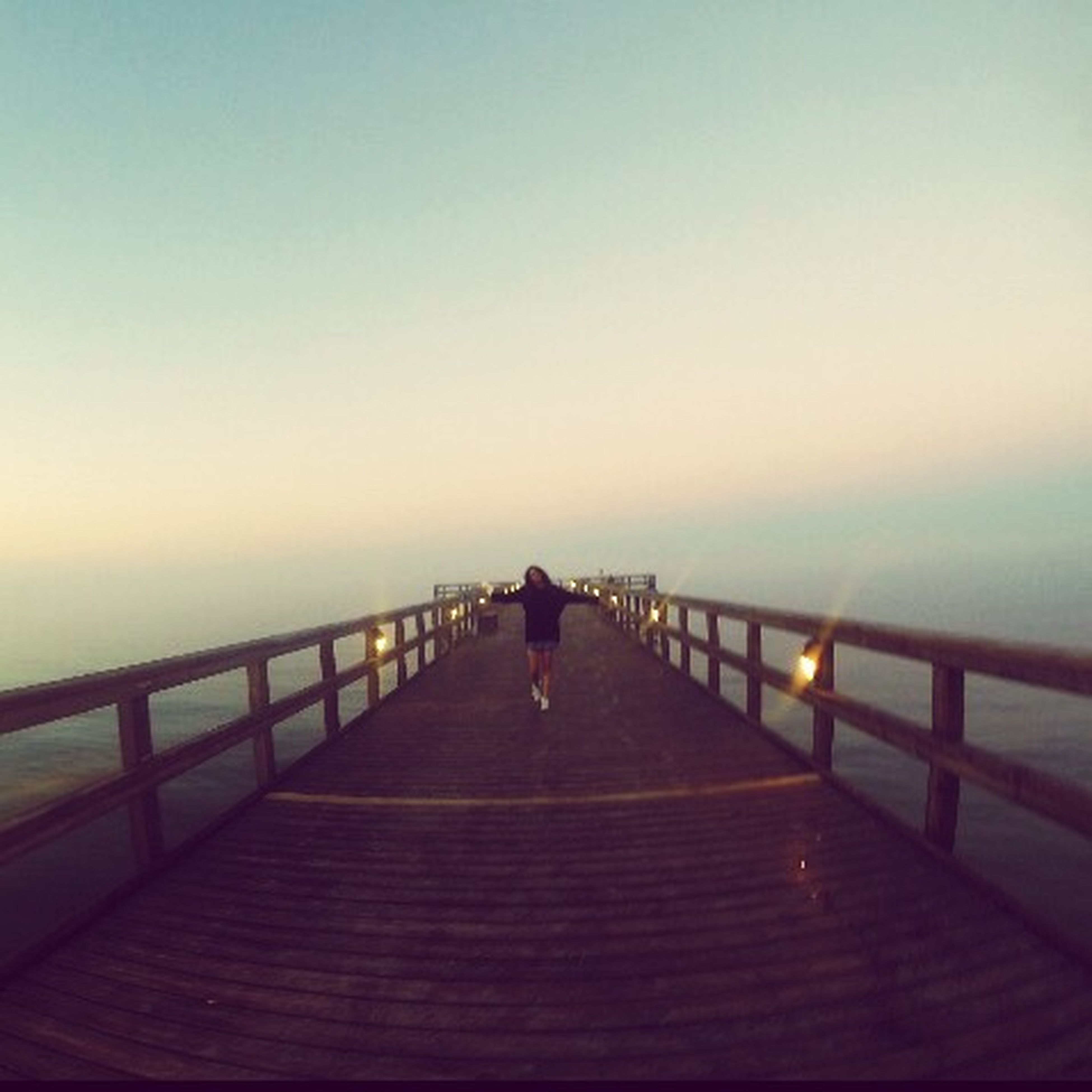 lifestyles, the way forward, full length, clear sky, sea, copy space, leisure activity, rear view, walking, railing, pier, men, water, sky, horizon over water, person, tranquility, boardwalk