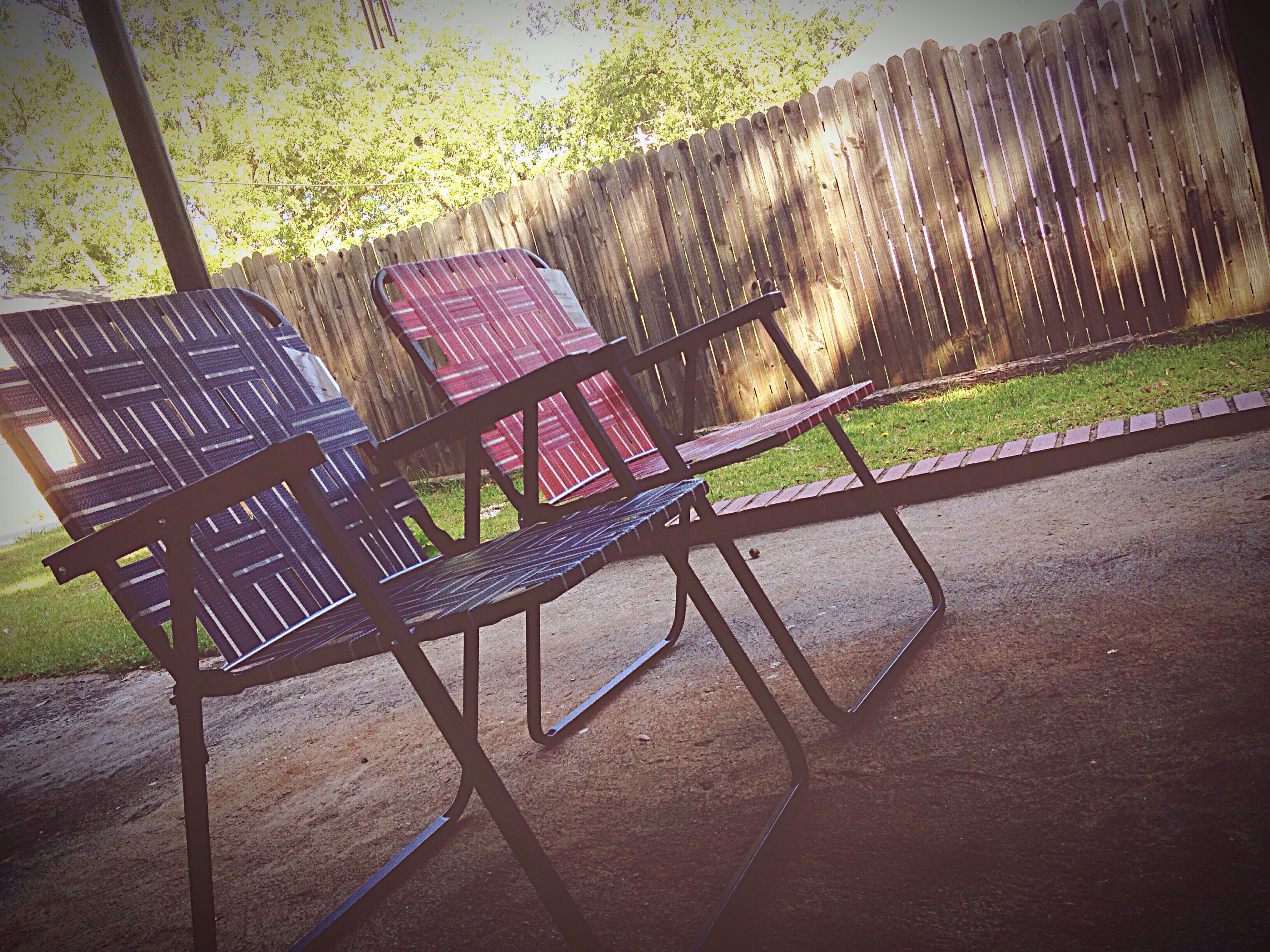 shadow, sunlight, empty, grass, chair, absence, bench, fence, metal, protection, seat, park - man made space, day, high angle view, outdoors, no people, sidewalk, green color, safety, built structure