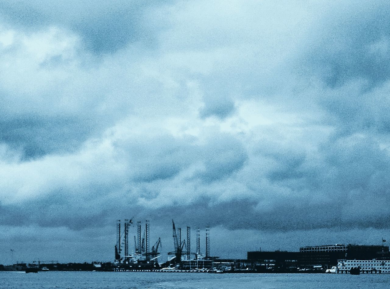 Scenic View Of Cloudy Sky Over Sea And City
