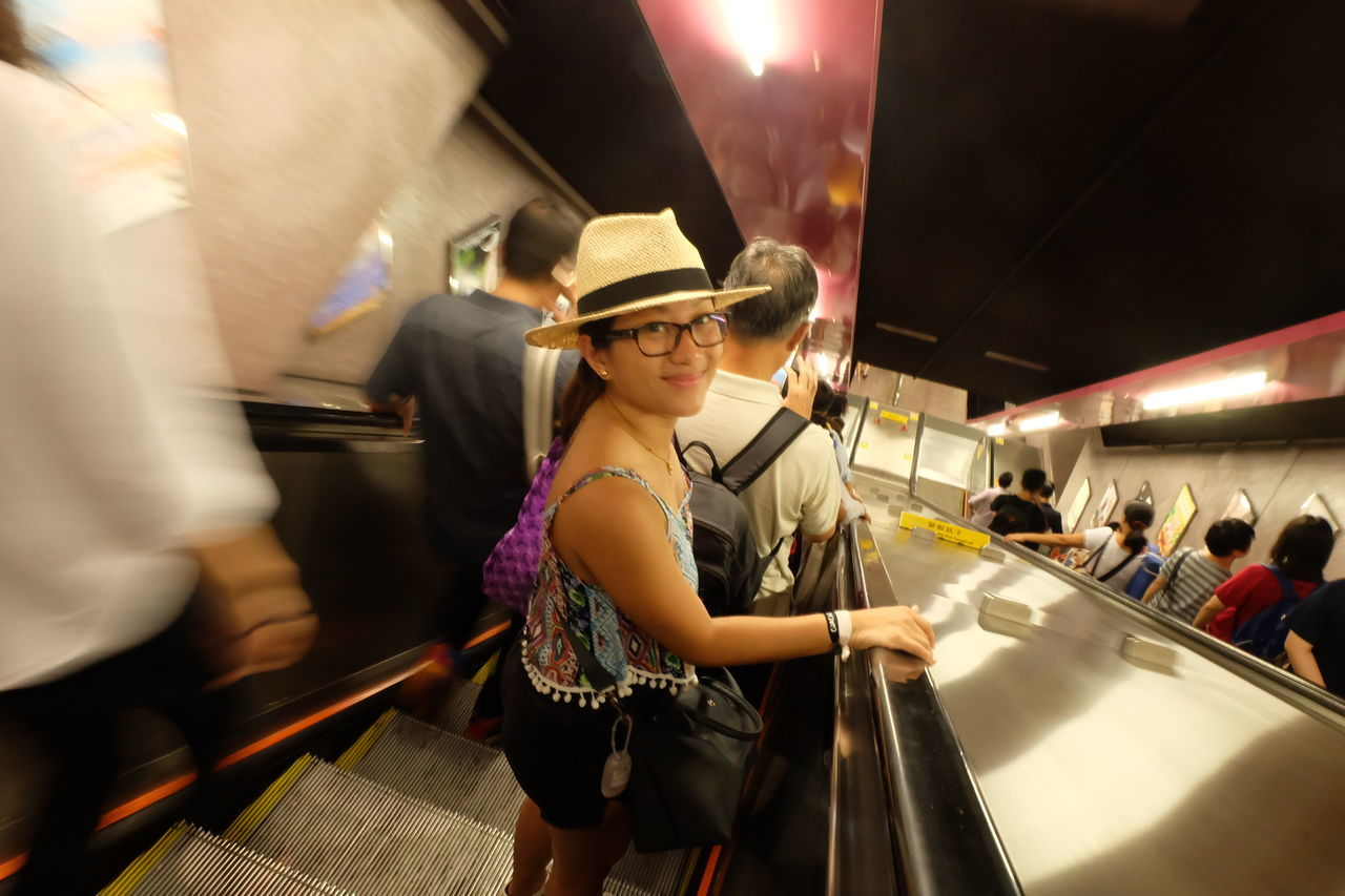 real people, hat, lifestyles, transportation, leisure activity, indoors, illuminated, women, standing, night, young women, young adult, headwear, people