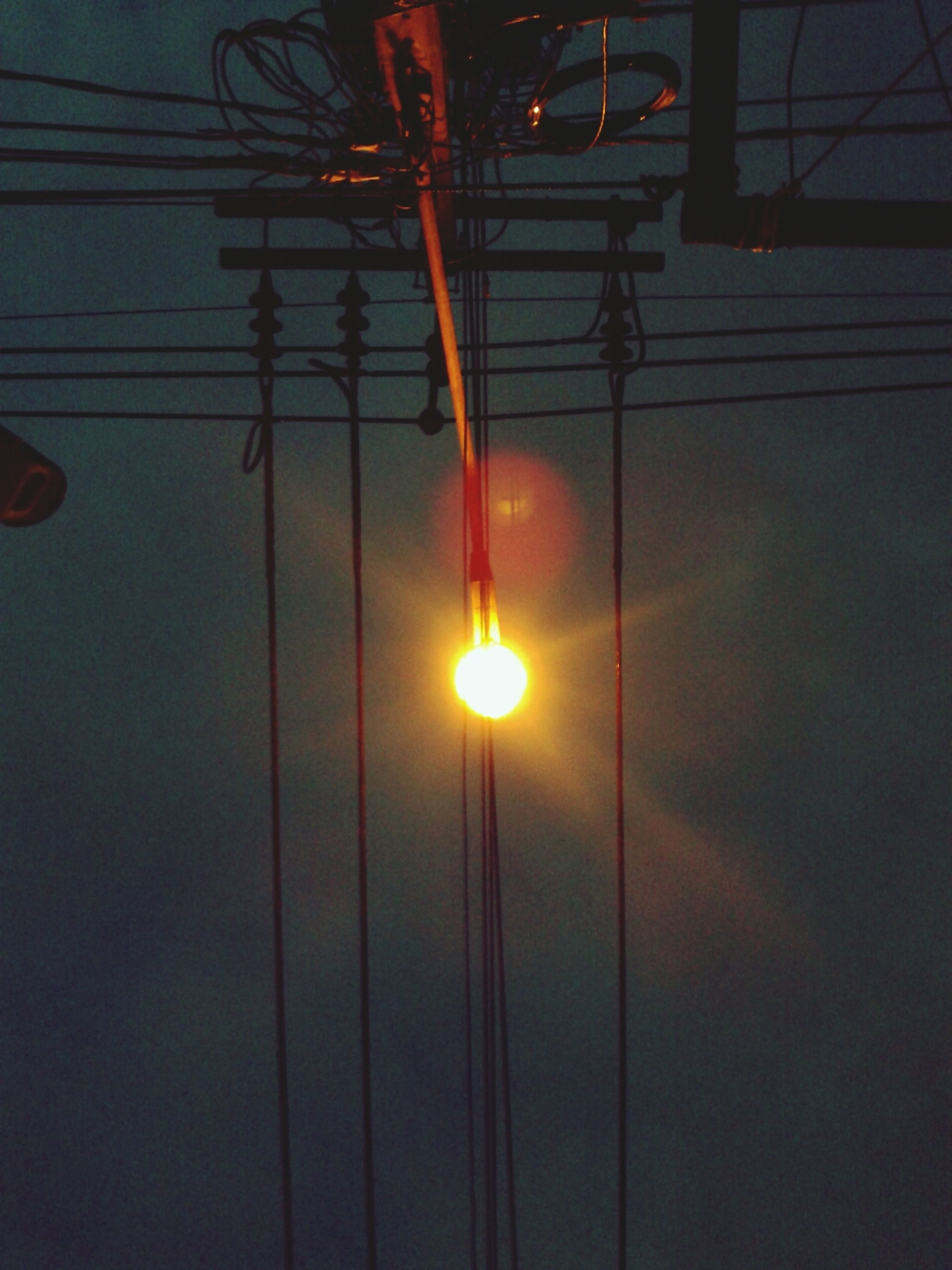 electricity, lighting equipment, illuminated, power line, low angle view, street light, silhouette, power supply, electricity pylon, cable, sunset, electric light, fuel and power generation, technology, connection, sky, night, light - natural phenomenon, sun, pole