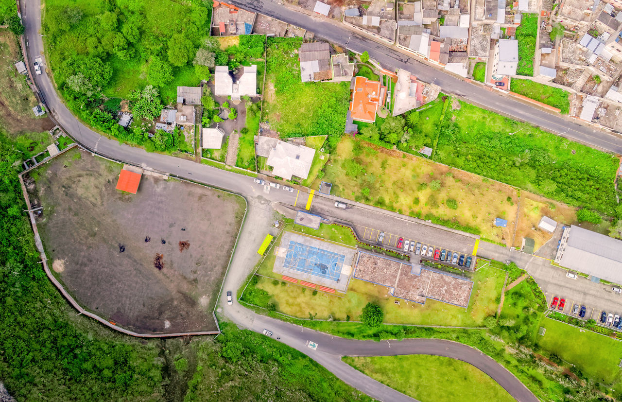 Aerial City View With Buildings And Parking Lots Of Banos De Agua Santa, Tungurahua Province, In The Daylight, South America Aerial Aerial Photography Aerial Shot Aerial View American Football Field Architecture Buiding City City City Life Cityscape Day Drone  Dronephotography Droneshot Golf Course Grass Green Green Color High Angle View Neighborhood No People Outdoors Sport Tree