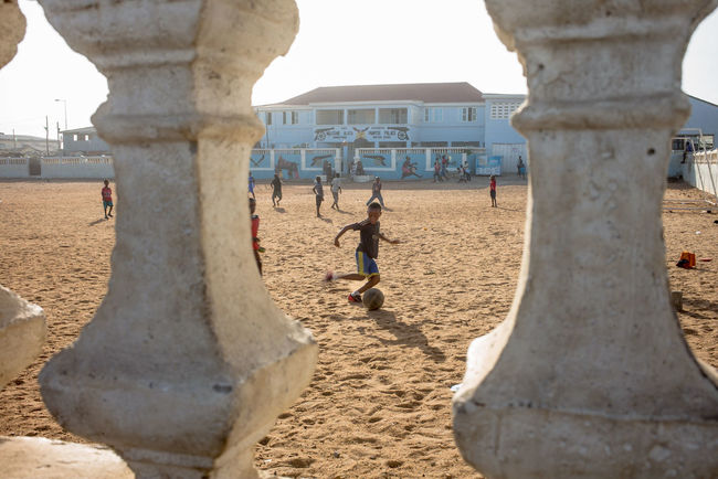 Africa Collection: West Africa, Ghana, Accra the Capital, Jamestown area, children playing their favourite sport soccer in front of the house of the area's chief Accra Active Africa Ball Built Structure Chief Dynamic Football Ghana House Outdoors Perspective Run Soccer Sport Tourism Travel Destinations West Africa Youth The Photojournalist - 2016 EyeEm Awards