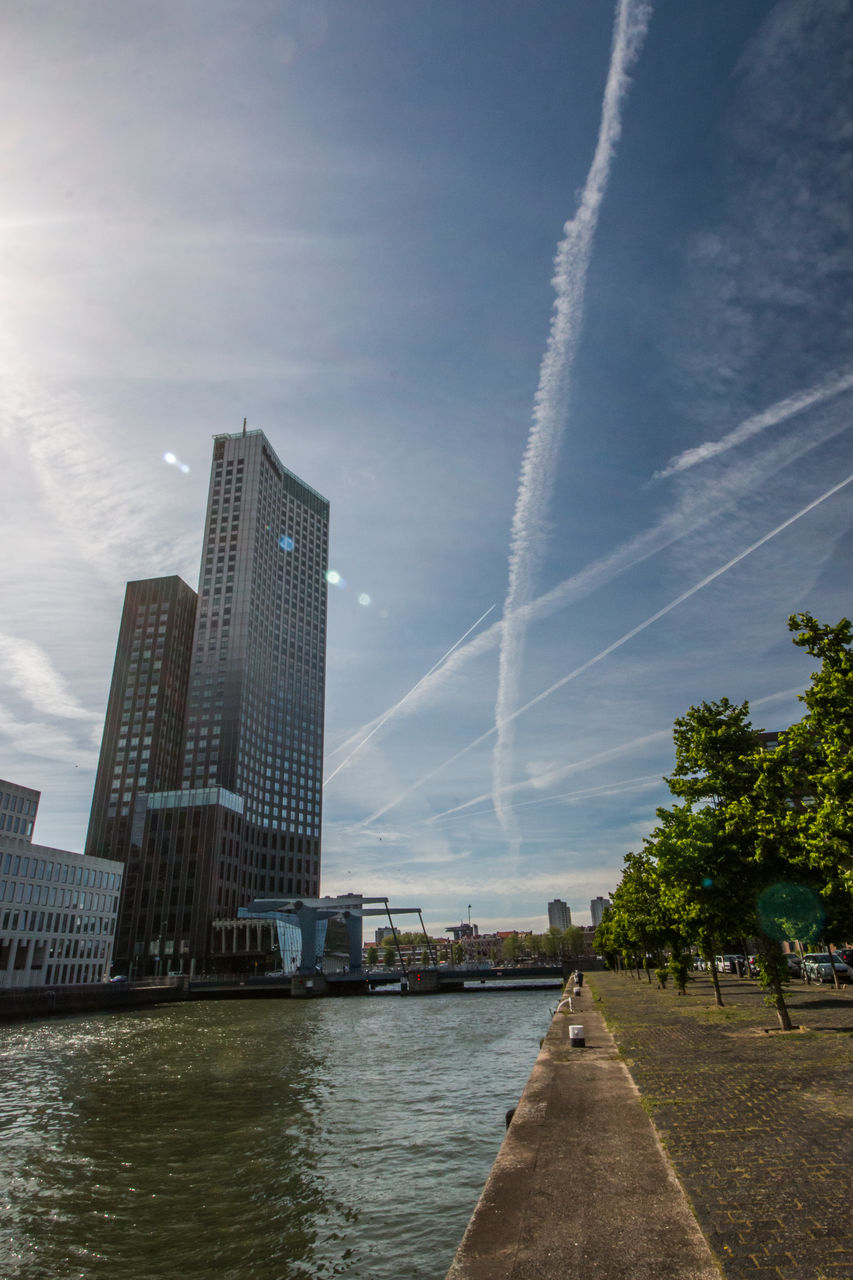 vapor trail, sky, built structure, water, architecture, river, building exterior, day, outdoors, no people, nature, tree, contrail, city