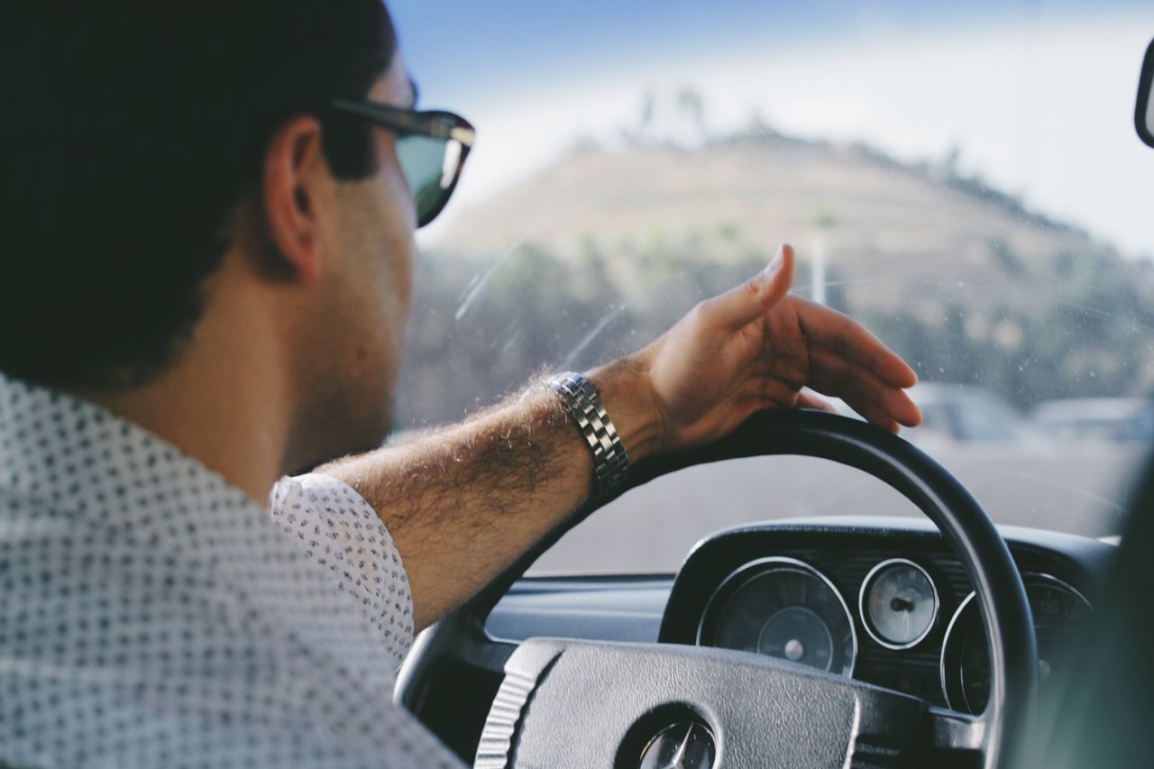 Cropped Image Of Man Holding Steering Wheel In Car