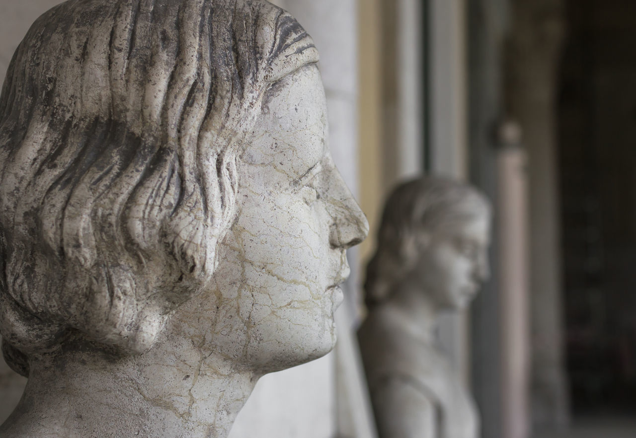 Statue of sad woman. Profile of young sad woman, in the background another statue of a woman and the hall of the museum. Ancient Antique Art Background Carved Classic Close-up Craftmanship Culture Decor European  Face Female Feminine  Gray Hall Handsome Heritage Human Image Italy Marble Masterpiece Mediterranean  Museum