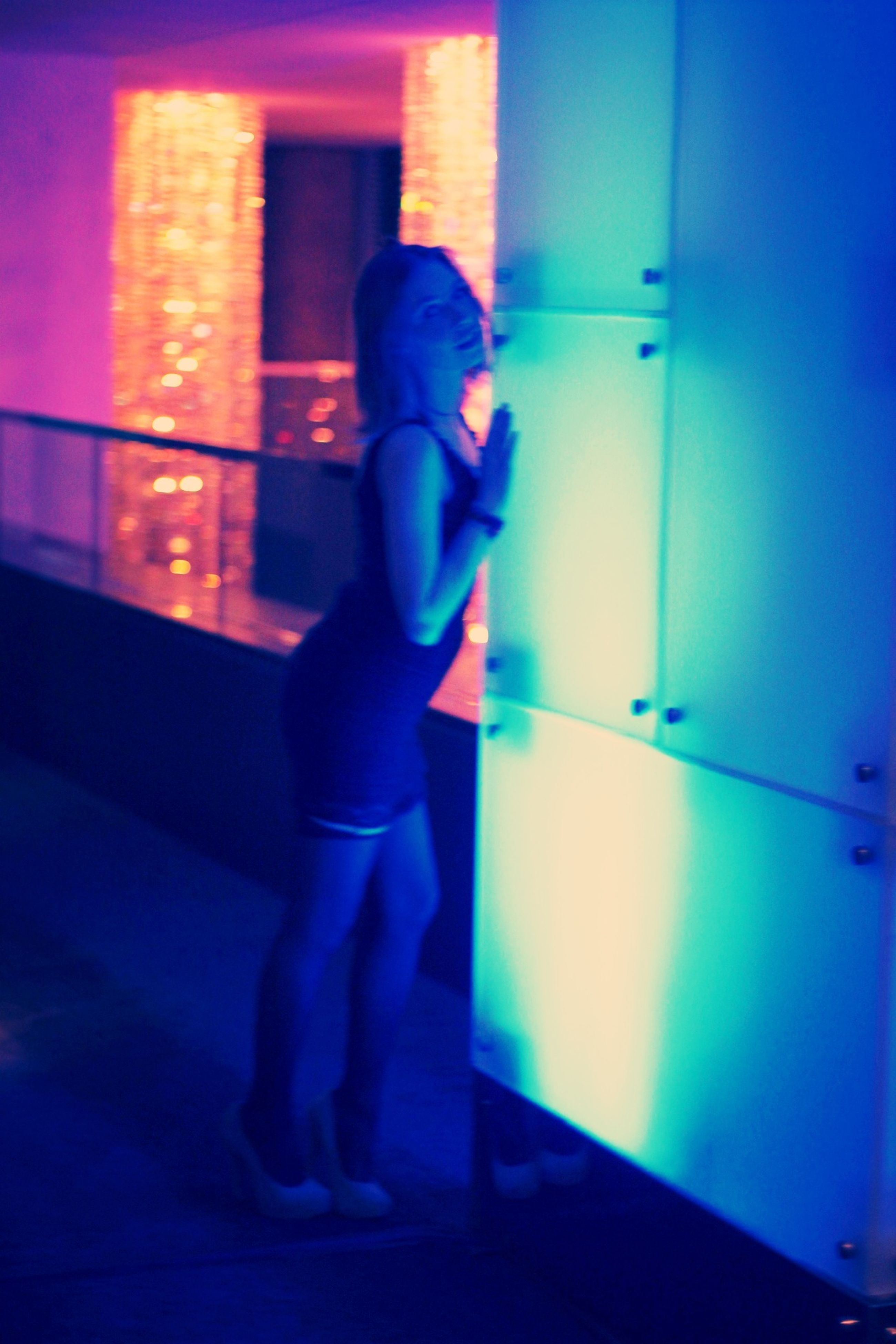 indoors, full length, lifestyles, rear view, illuminated, men, standing, night, casual clothing, leisure activity, walking, built structure, architecture, blue, silhouette, person, side view