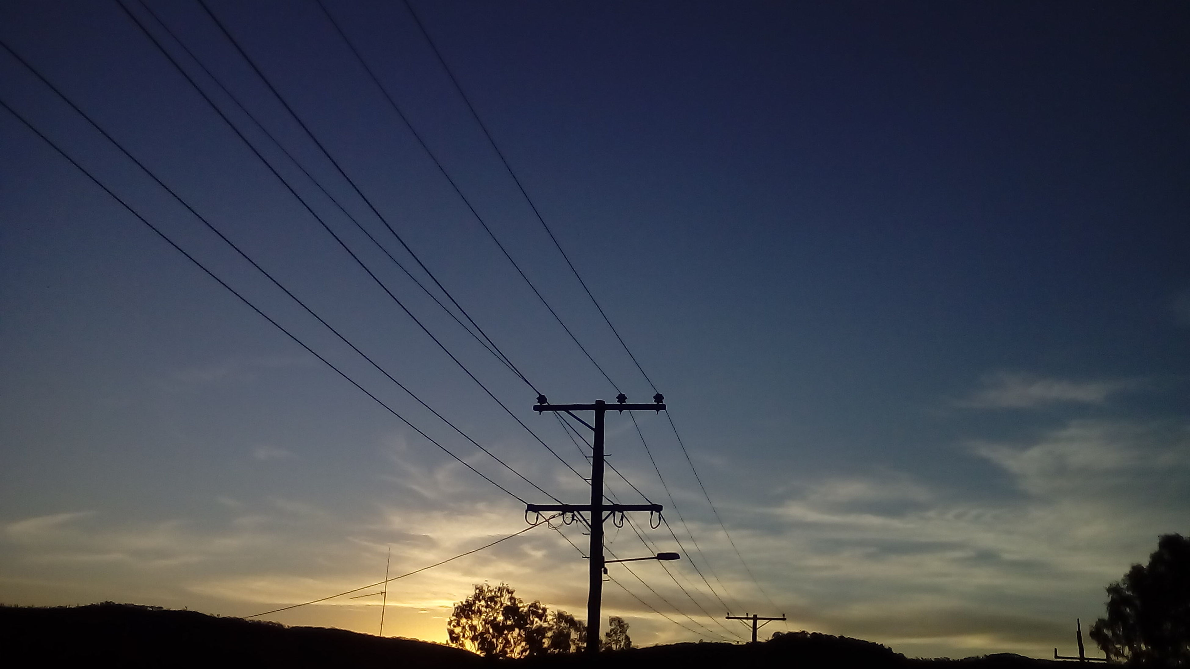 power line, electricity pylon, power supply, electricity, cable, fuel and power generation, connection, silhouette, technology, low angle view, sky, sunset, power cable, tranquility, tree, scenics, tranquil scene, dusk, nature, beauty in nature