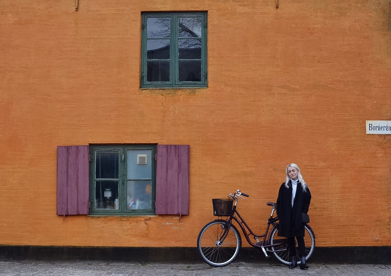 Nyboder Copenhagen Portait Portrait Of A Woman Bike Bikes Orange Orange Color Historic Colors Color Portrait Girl Woman Outdoor Photography Architecture Photooftheday Eye4photography  EyeEm Masterclass Travel Building Traveling Shootermag EyeEm Best Shots Person Windows