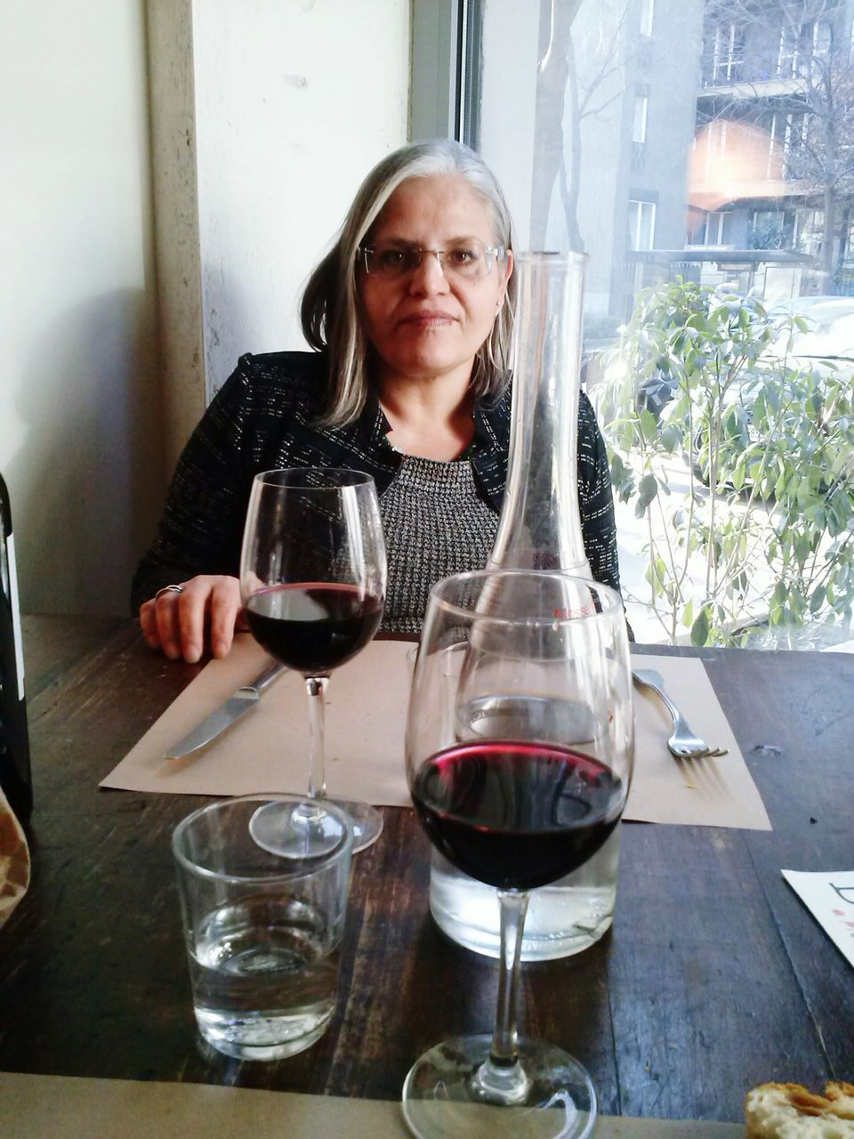 wineglass, wine, table, red wine, one person, real people, alcohol, eyeglasses, looking at camera, drink, indoors, drinking glass, portrait, holding, leisure activity, lifestyles, happiness, women, day, adult, people
