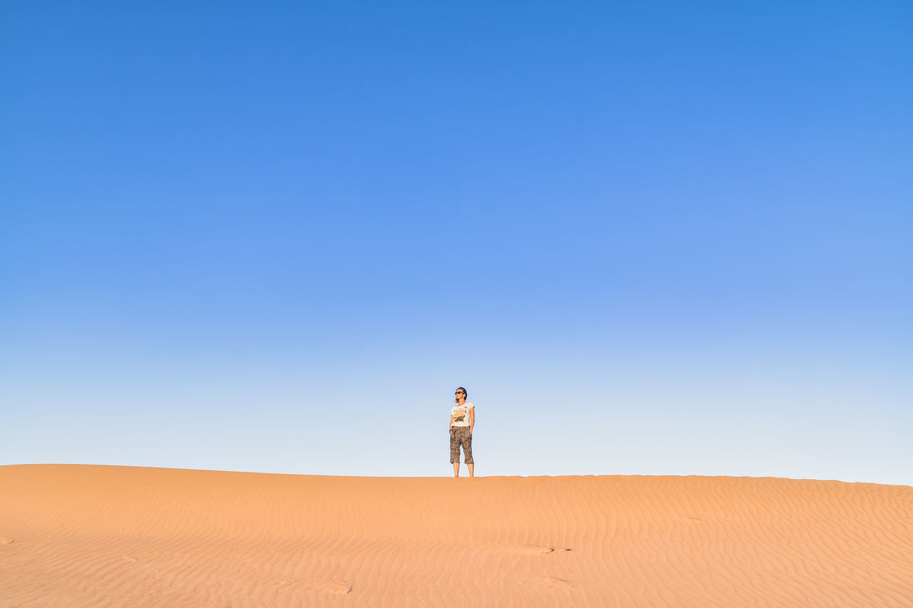 Adult Arid Climate Clear Sky Desert Desert Desert Beauty Dry Landscape Nature Oman Outdoors Sand Sand Dune Sky Summer Sunlight Sunny Travel Travel Destinations Travel Photography Live For The Story